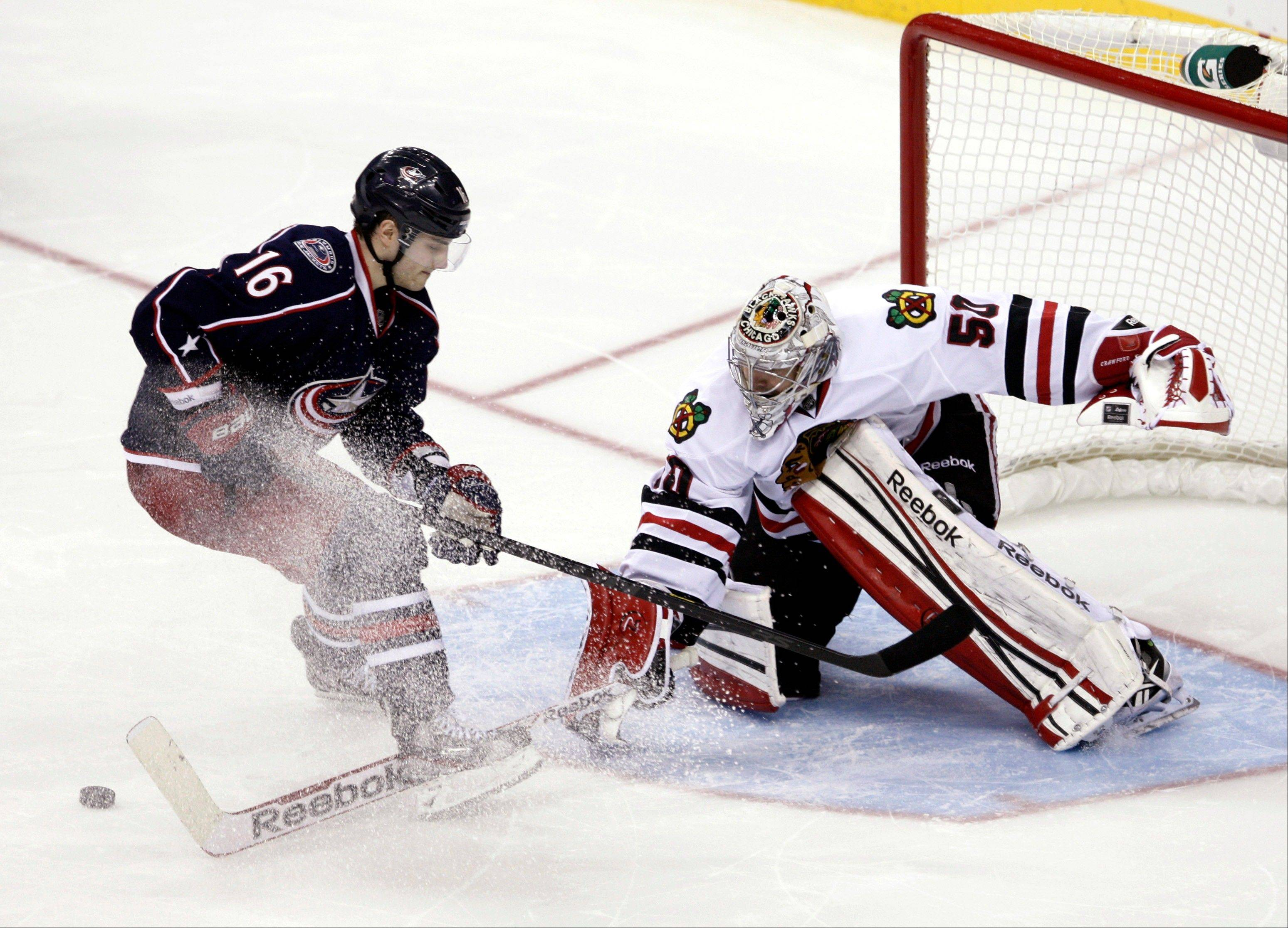 Blackhawks goalie Corey Crawford, right, stops a shot by Columbus Blue Jackets' Derick Brassard in the shootout of an NHL hockey game in Columbus, Ohio, Thursday, March 14, 2013. The Blackhawks won 2-1.