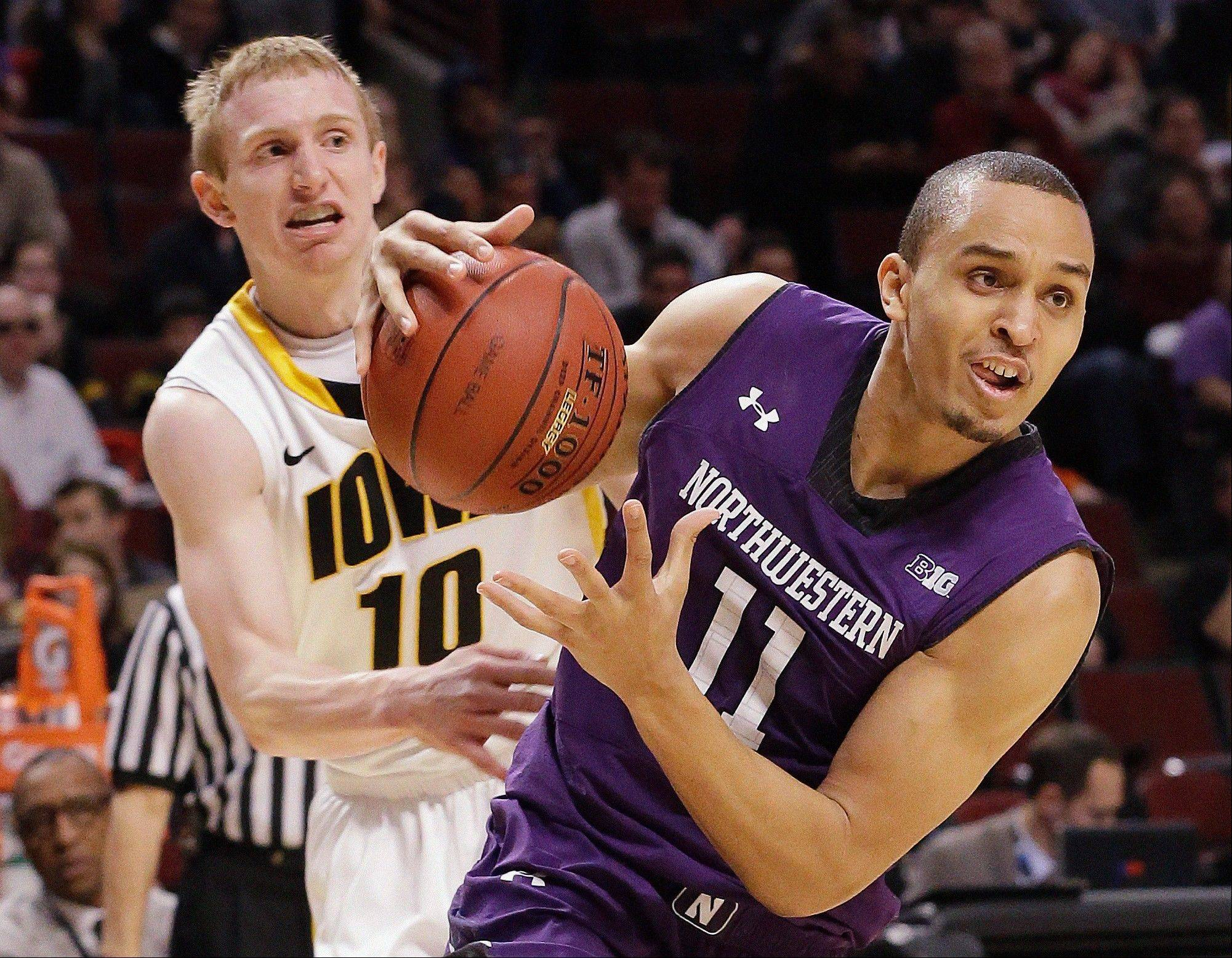 Northwestern's Reggie Hearn (11) drives past Iowa's Mike Gesell during the first half.