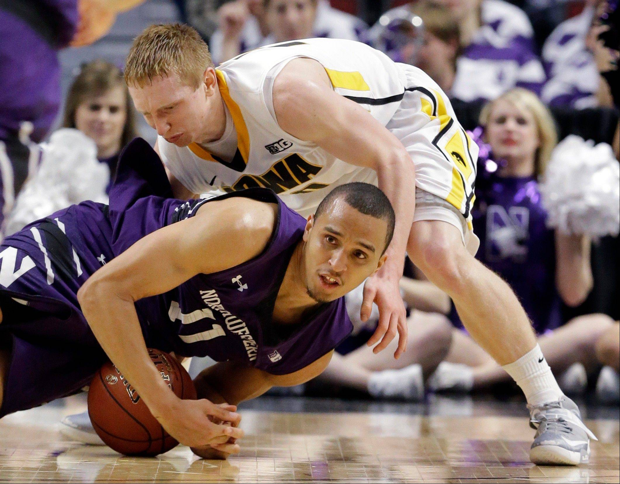 Northwestern's Reggie Hearn (11) and Iowa's Aaron White battle for a loose ball during the second half.