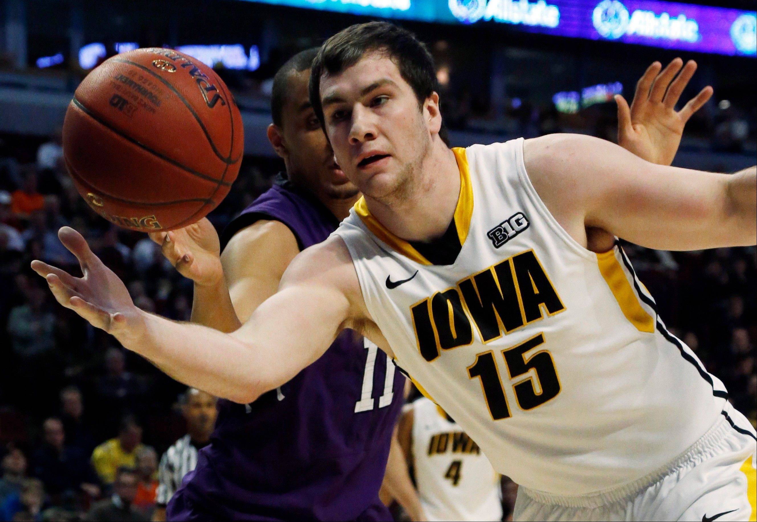 Iowa's Zach McCabe (15) and Northwestern's Reggie Hearn (11) go after a loose ball.