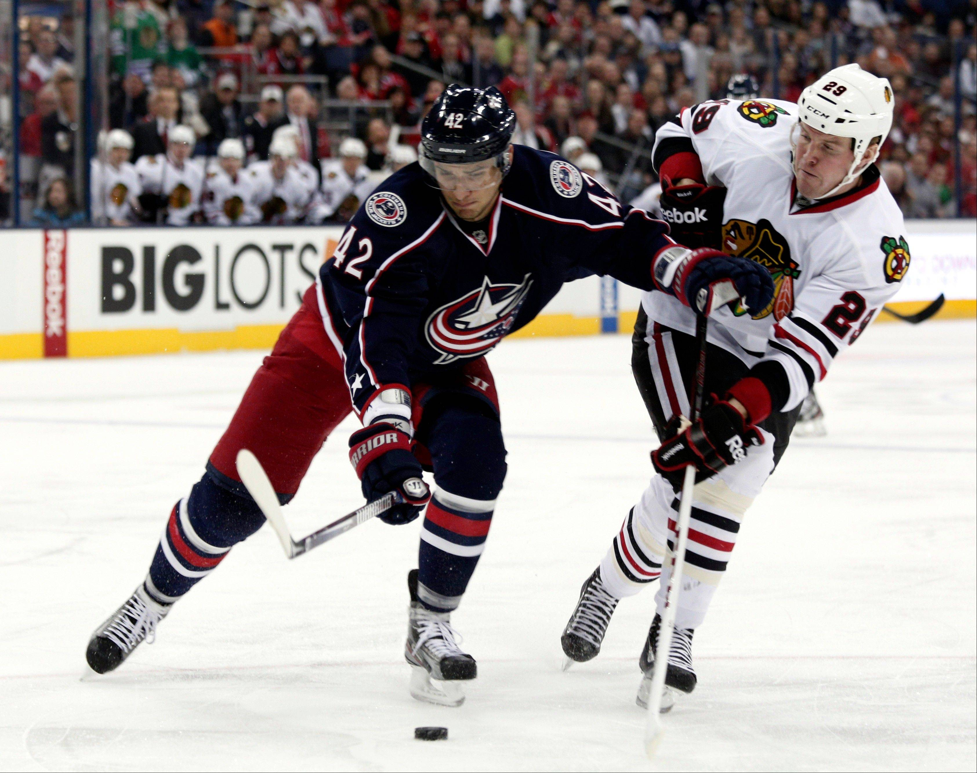 Columbus Blue Jackets' Artem Anisimov, left, of Russia, works for the puck against Chicago Blackhawks' Bryan Bickell during the first period.