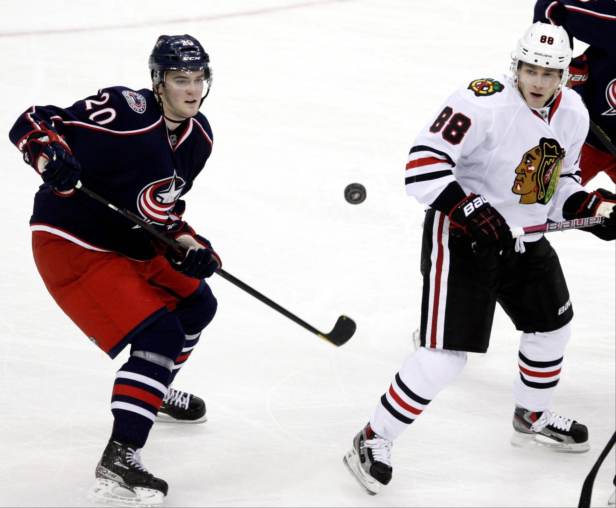 Chicago Blackhawks' Patrick Kane, right, and Columbus Blue Jackets' Tim Erixon work for the puck during the third period.