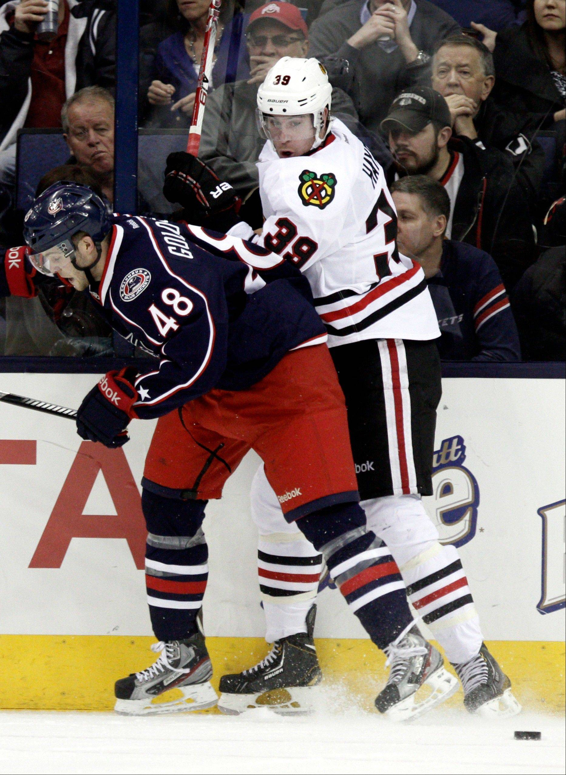 Columbus Blue Jackets' Cody Goloubef, left, and Chicago Blackhawks' Jimmy Hayes work for the puck in the second period.