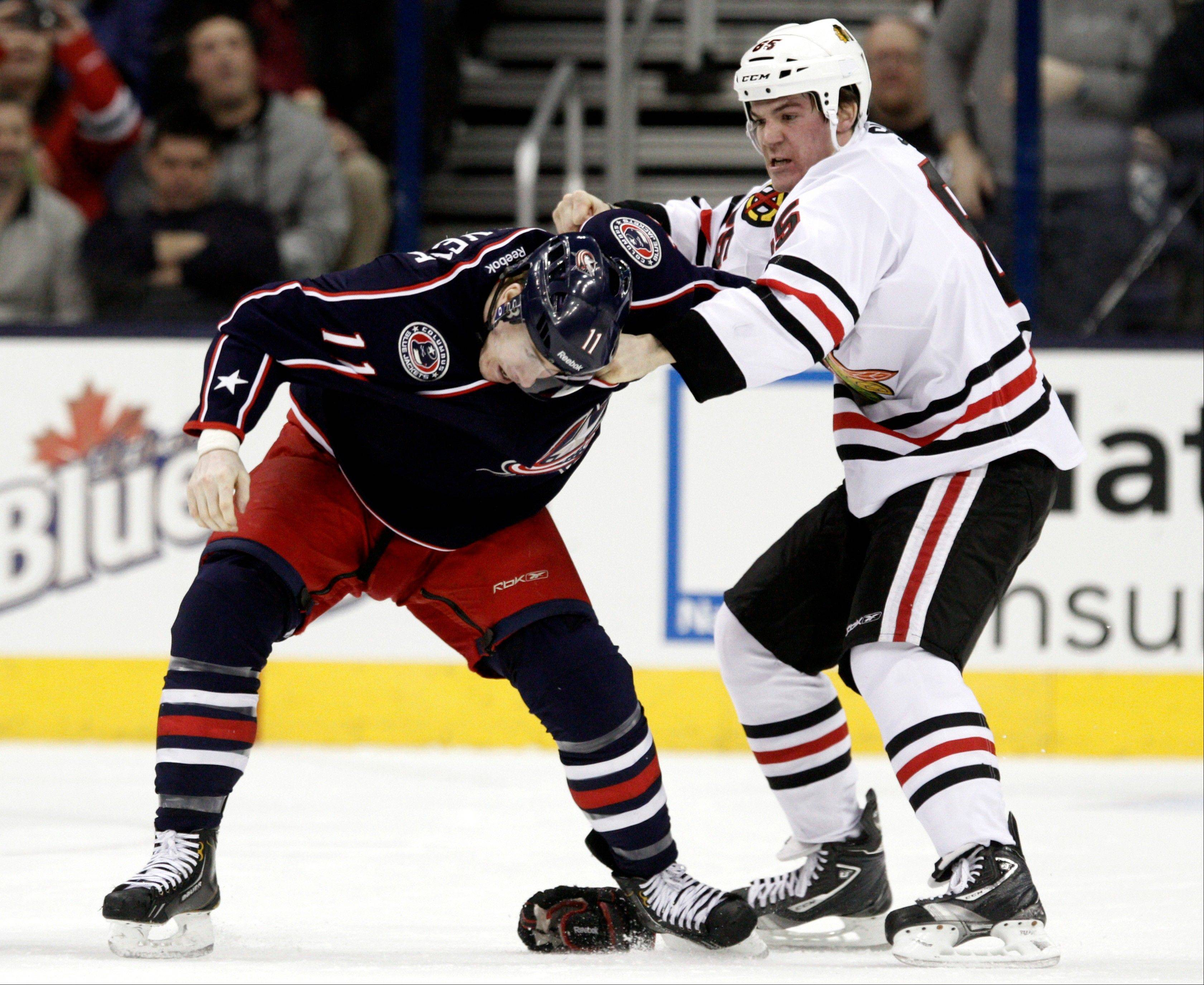 Chicago Blackhawks' Andrew Shaw, right, fights with Columbus Blue Jackets' Matt Calvert during the first period.