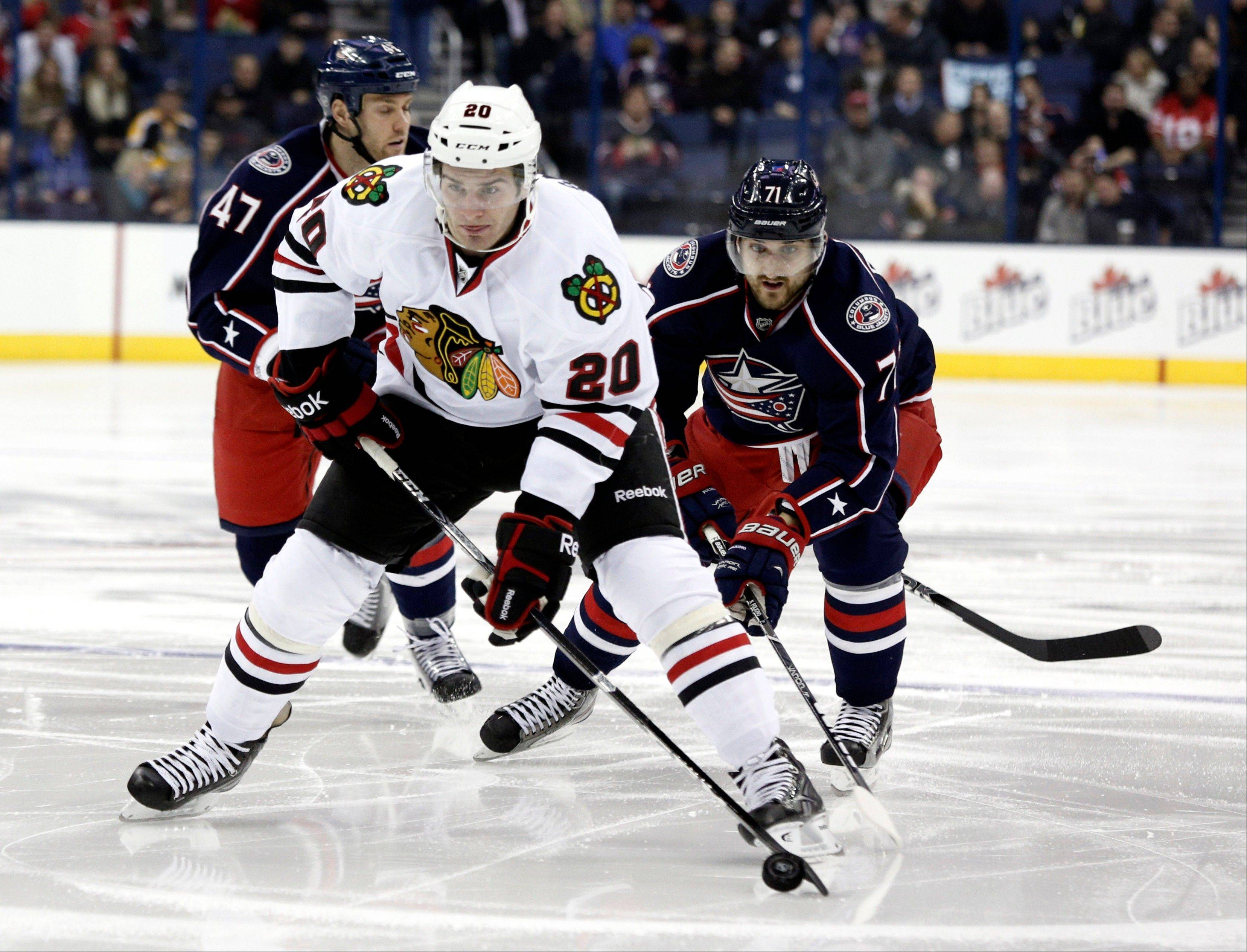 Chicago Blackhawks' Brandon Saad (20) carries the puck against Columbus Blue Jackets' Dalton Prout (47) and Nick Foligno (71) during the first period.