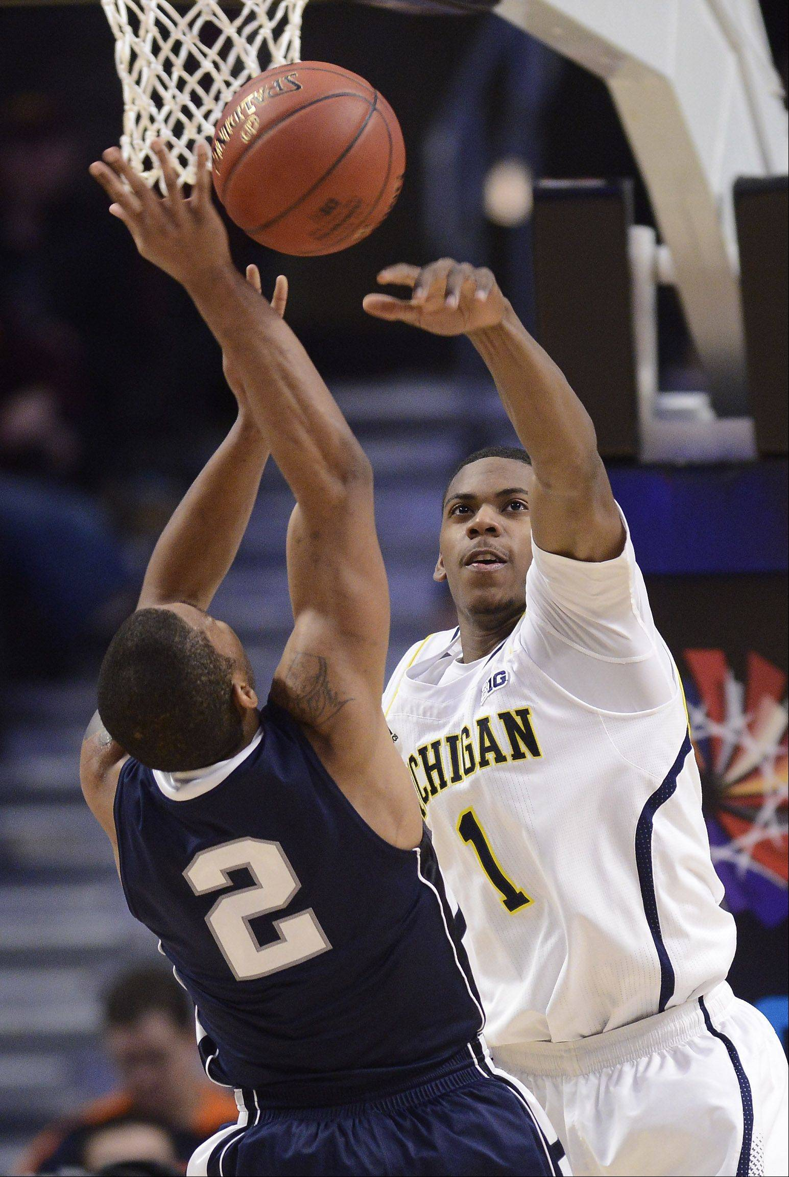 Michigan's Glenn Robinson III, right, blocks a shot by Penn State's D.J. Newbill.