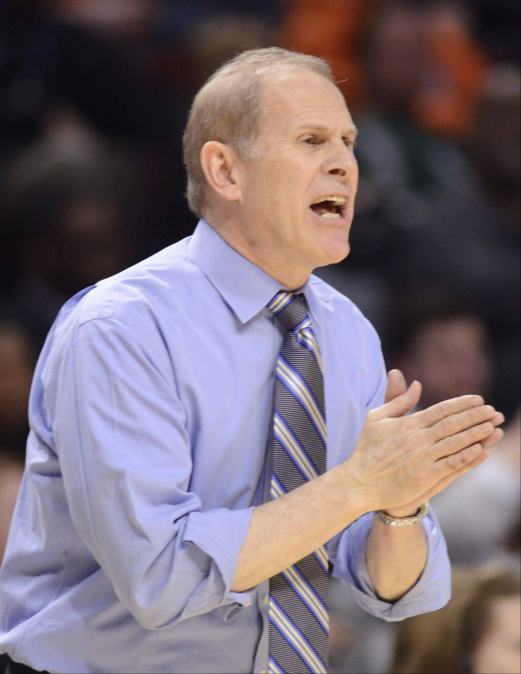 Michigan coach John Beilein guides his team.