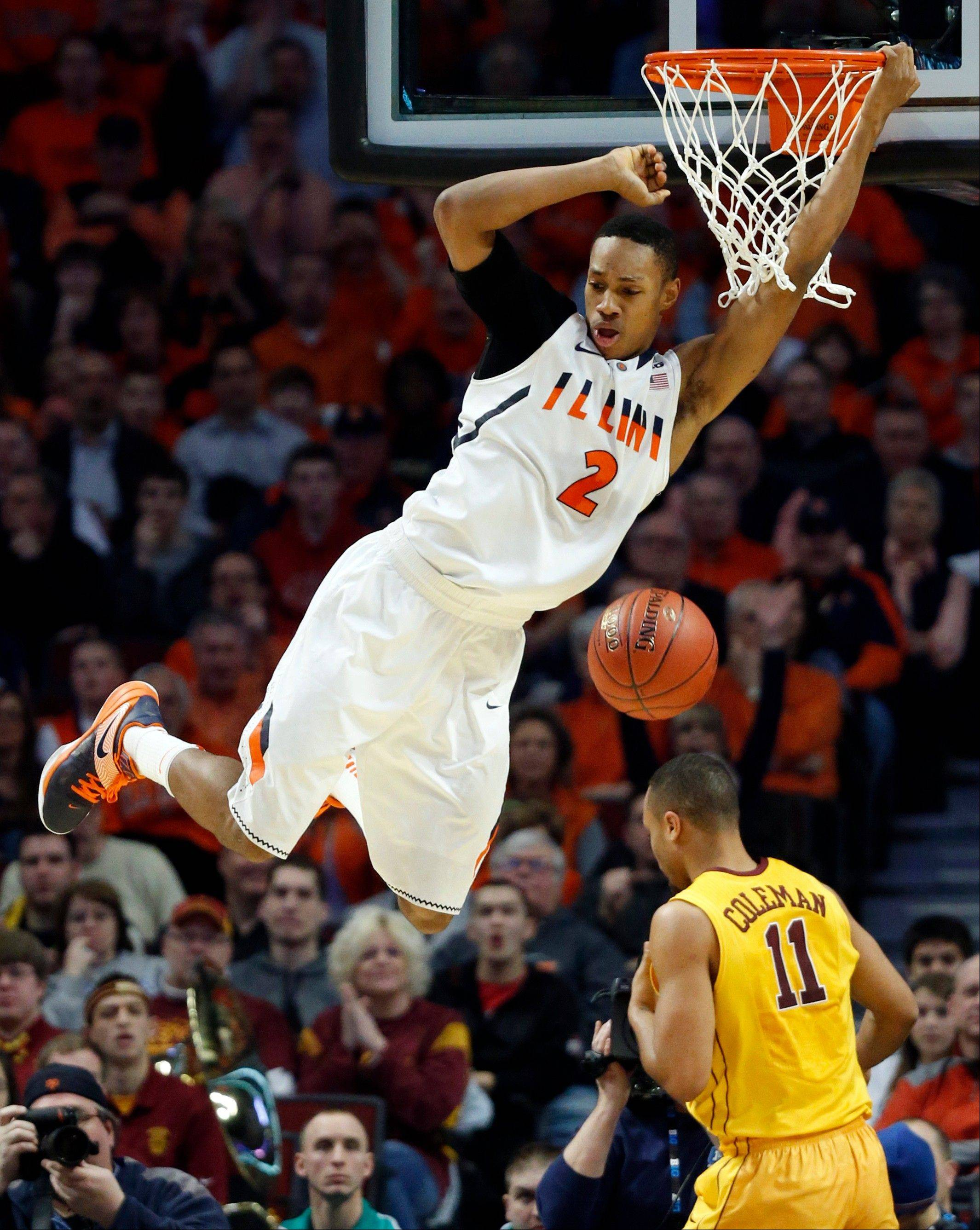 Illinois' Joseph Bertrand (2) dunks over Minnesota's Joe Coleman (11) during the first half.