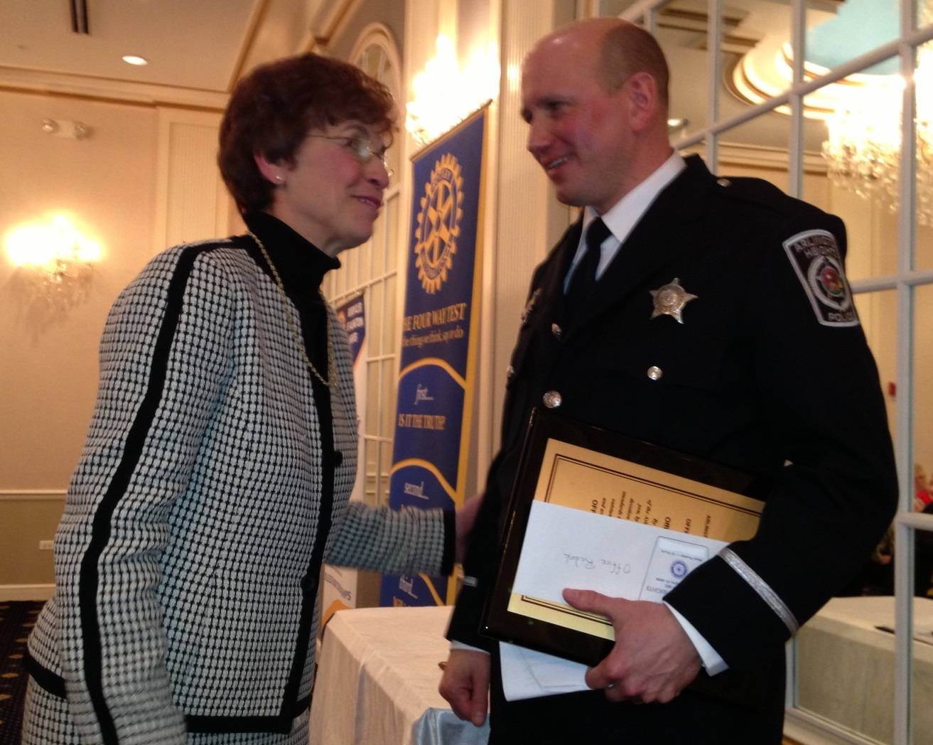 Arlington Heights mayor Arlene Mulder congratulates police officer Todd Radek after presenting him with the L.W. Calderwood Officer of the Year Award.