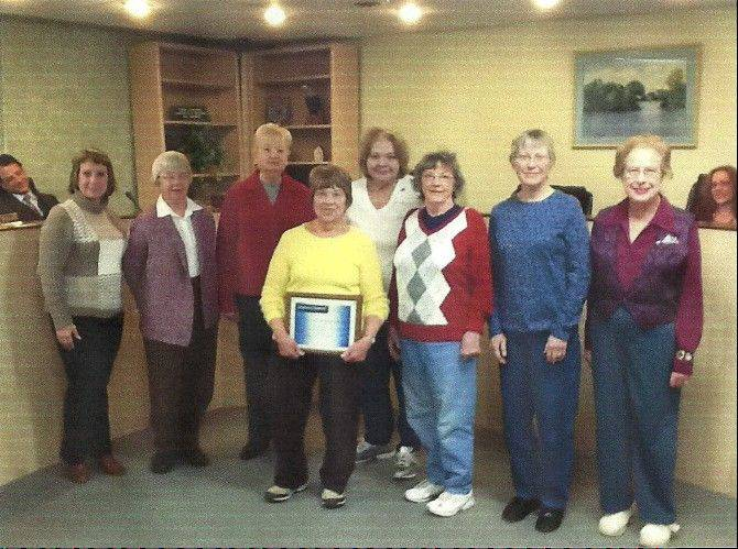 From left, Island Lake Village Attorney David Silverman; Mayor Debbie Hermann; Woman's Club members Ann Murray, Kay Kolacki, President Joan Kreiling holding plaque, Merrily Fantus, Juel Olmsted, Linda Gore and Dona Willard; and Village Trustee Shannon Fox.