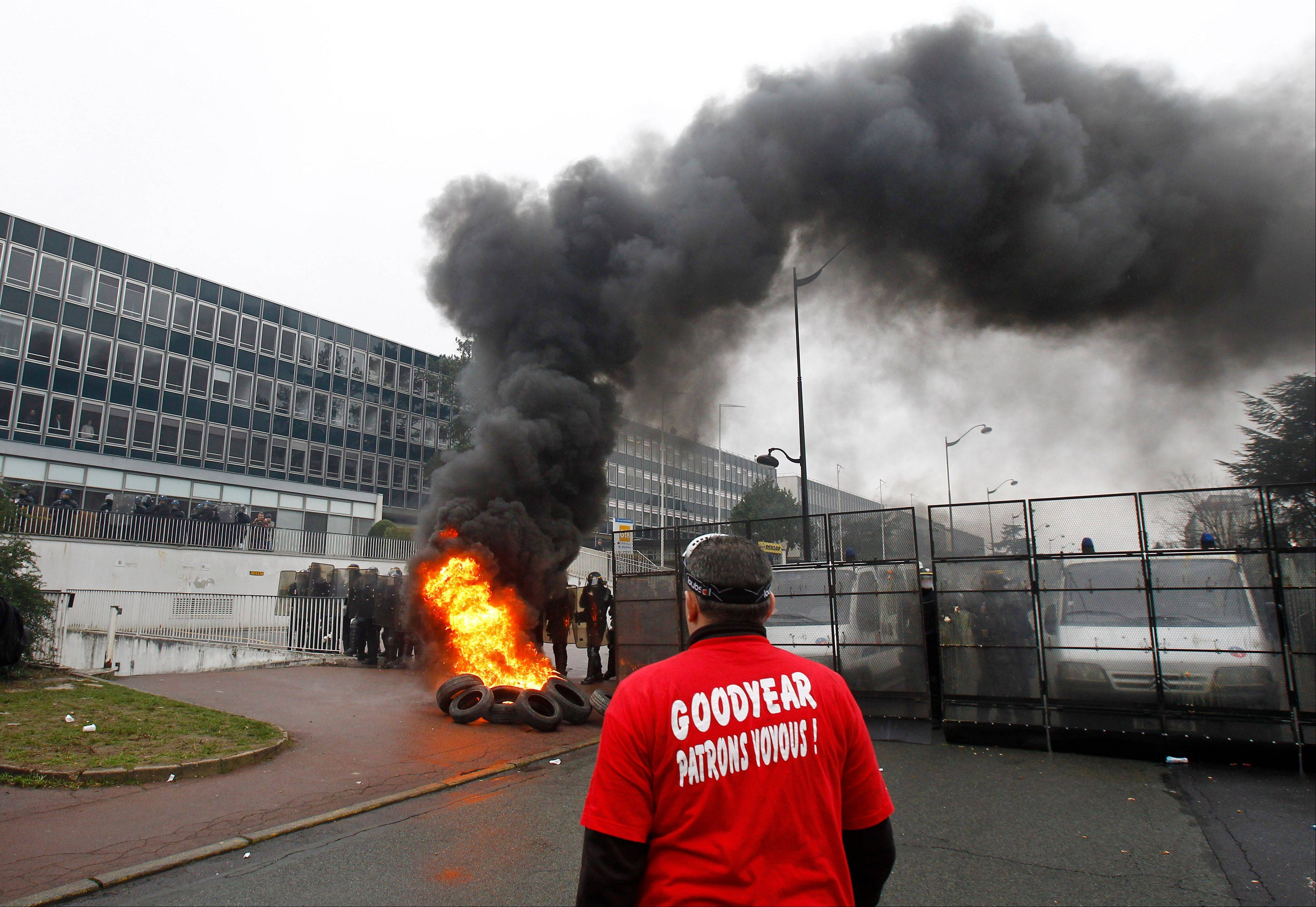 A Goodyear worker wearing a tee shirt reading �Goodyear, thug bosses� stands near burning tires, as police officers form a line during a demonstration against layoffs, at the Goodyear headquarters in Rueil Malmaison, west of Paris. Tensions � and even confrontation � between unions and management have long been the norm in France.