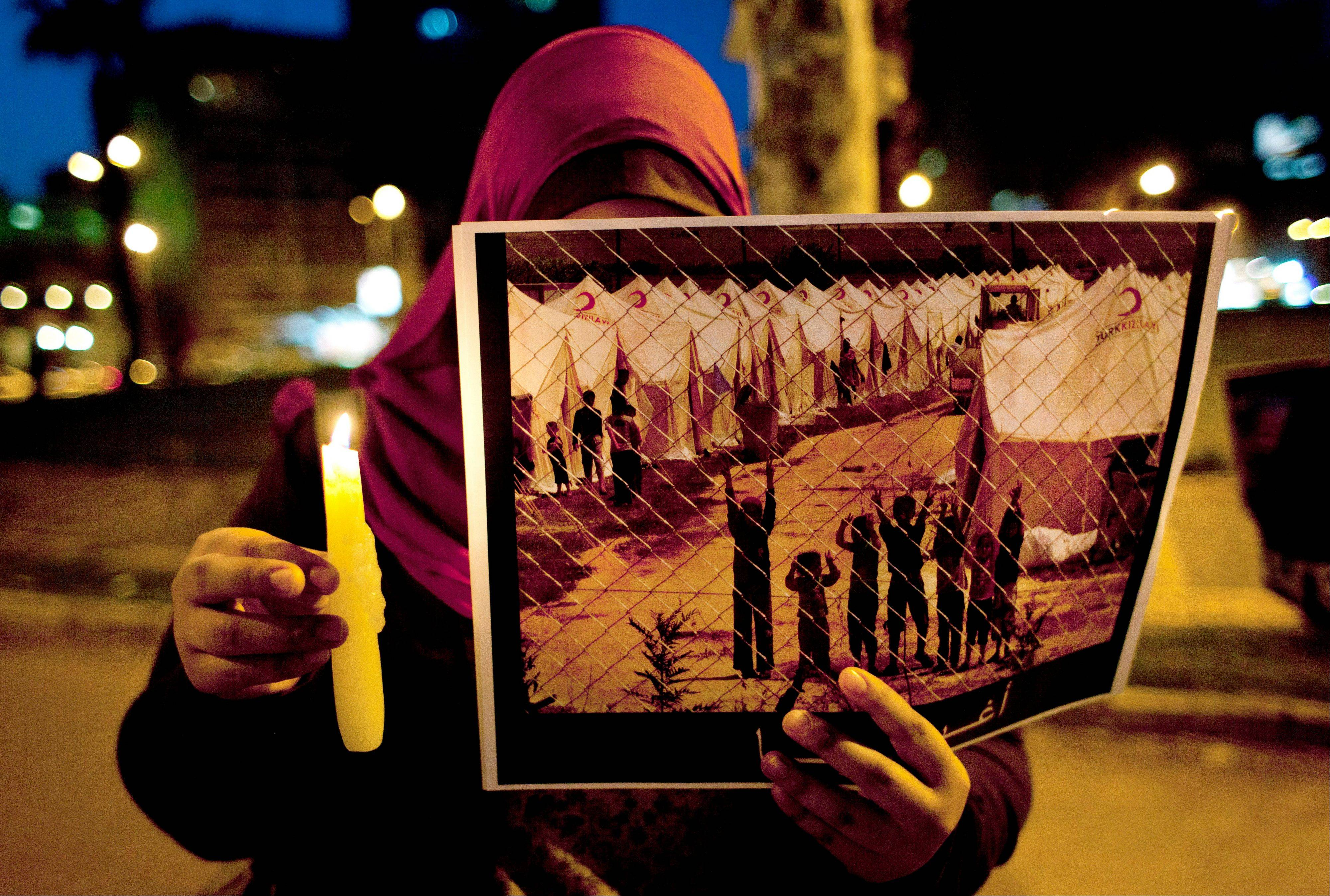A protester holds a poster with partial Arabic that reads, �rescue us,� during the candlelit vigil, marking the second anniversary of the Syrian revolution, in Cairo, Egypt, Thursday, March 14, 2013.