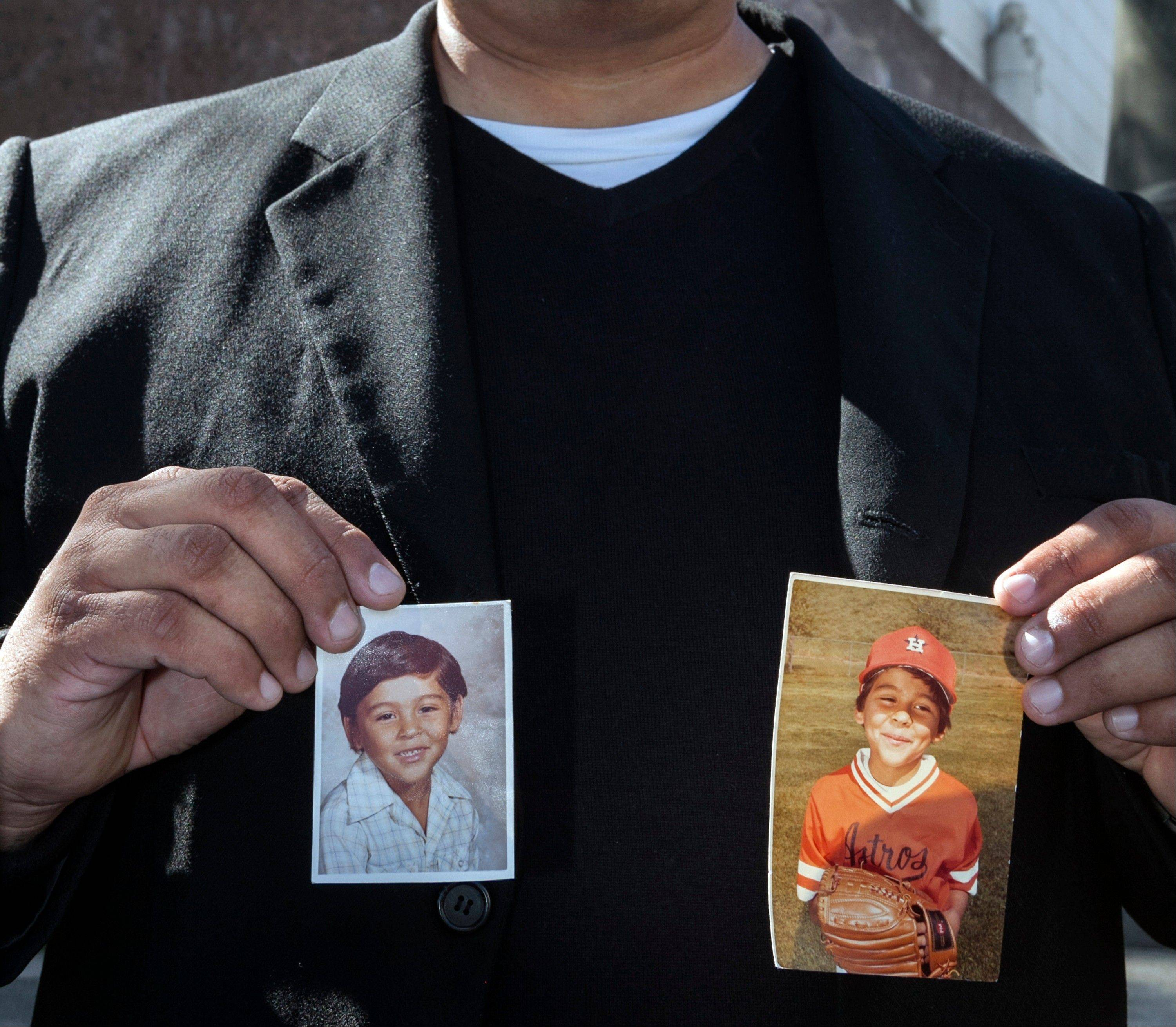 Michael Duran, a plaintiff in a sex abuse settlement with the Roman Catholic Archdiocese of Los Angeles, holds up pictures of himself when he was a child during a news conference to announce details of a nearly $10 million settlement of their lawsuits against the Archdiocese of Los Angeles Thursday, March 14, 2013. The U.S. church�s challenges include recovering from the clergy sexual abuse scandal, which has resulted in the bankruptcies of prominent archdioceses and cost the Church in America an estimated $3 billion in legal settlements.