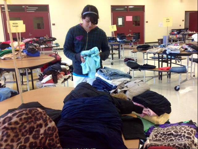 John T. Magee Middle School in Round Lake will host a clothing giveaway during parent-teacher conferences Thursday. A student, pictured, is helping sort clothes at the school�s last event in October.