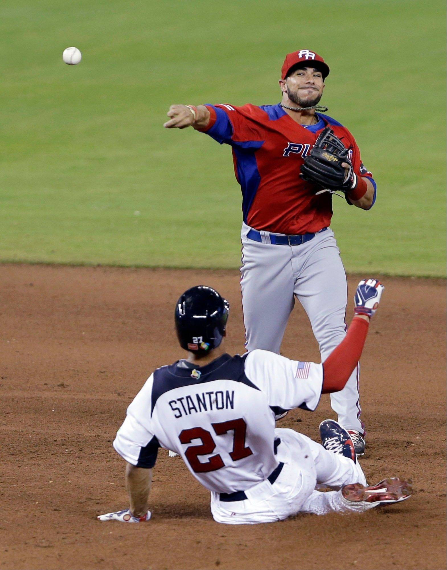 Puerto Rico shortstop Mike Aviles throws to first to attempt a double play as United States' Giancarlo Stanton (27) slides into second during the seventh inning of the second-round elimination game of the World Baseball Classic, Friday, March 15, 2013, in Miami. United States' Ben Zobrist was safe at first and Stanton out at second base and Puerto Rico defeated the U.S. 4-3. (AP Photo/Wilfredo Lee)