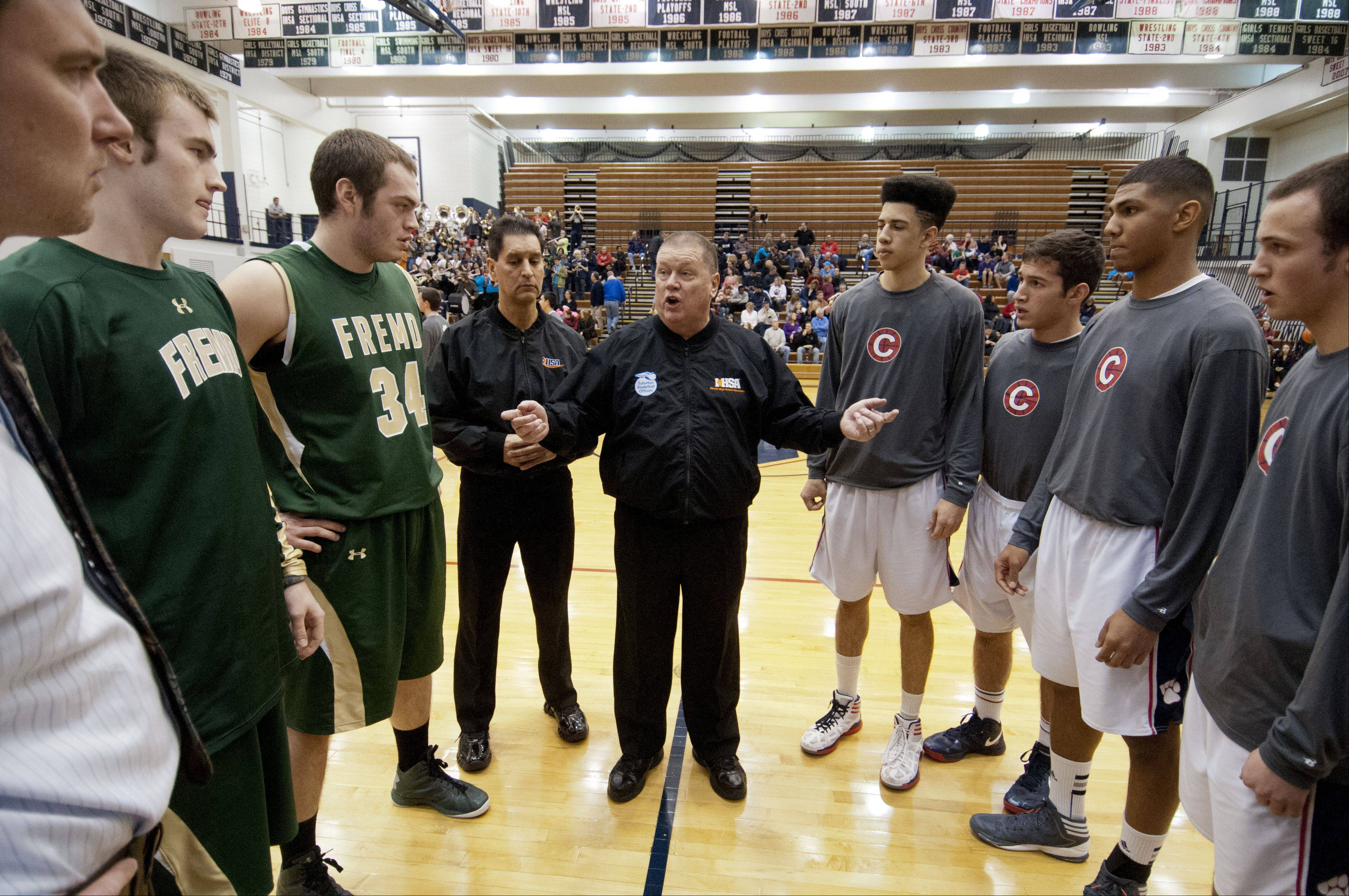 Bieterman talks to the team captains before a game between Fremd and Conant high schools.