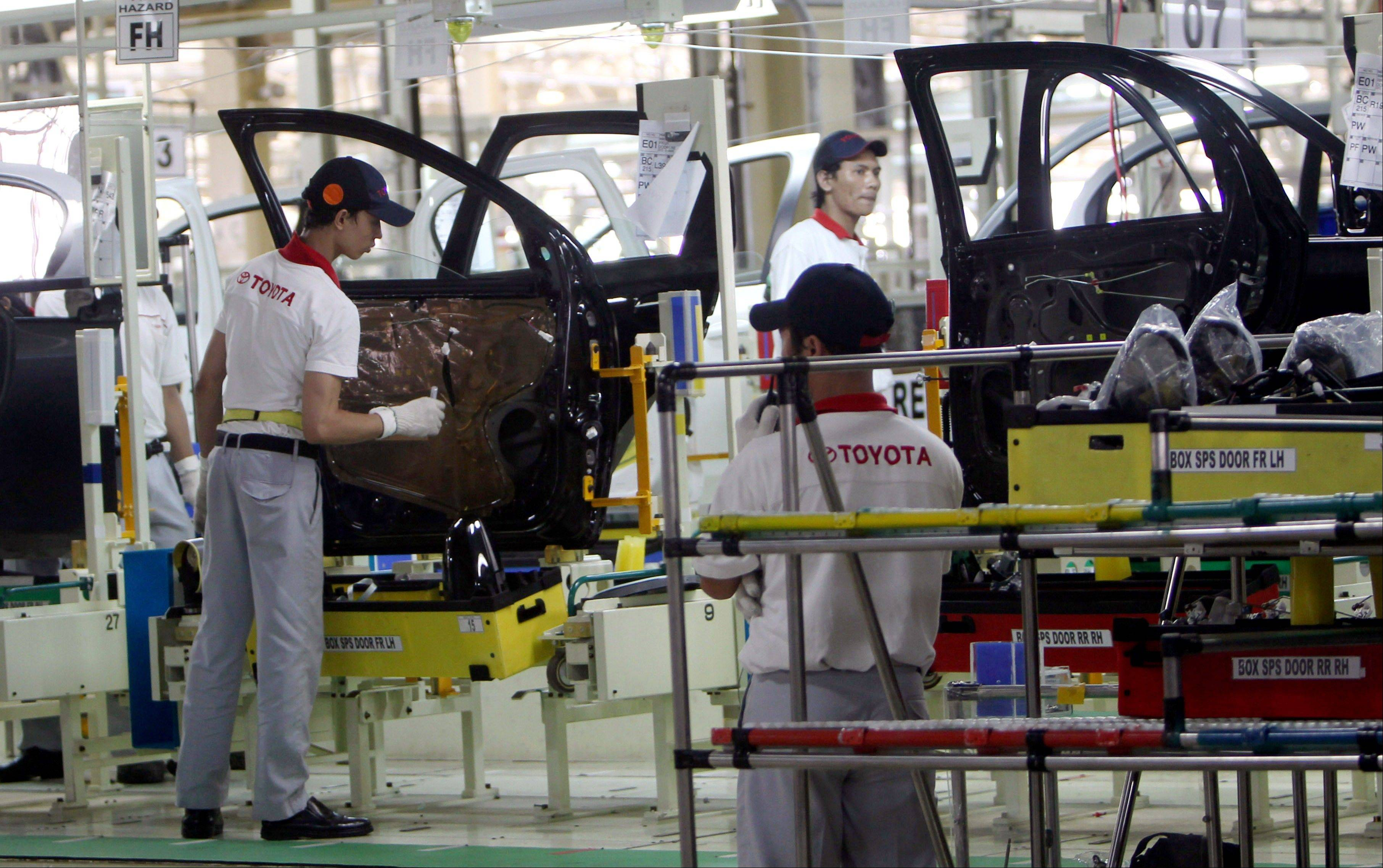 Workers assemble passenger cars Friday at the new Toyota plant in Karawang, West Java, Indonesia. Toyota officially opened their second manufacturing plant in the country to increase their total production capacity to more than 200,000 cars a year by 2014.