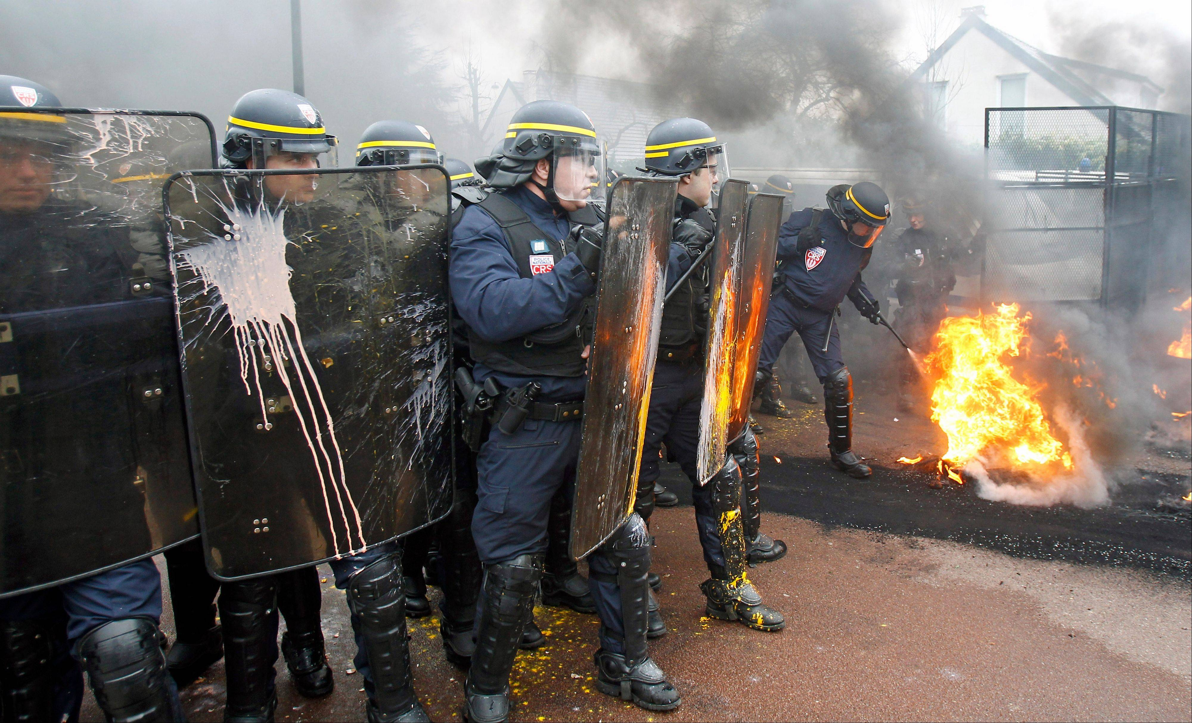 A riot police officer extinguishes burning tires during a demonstration by Goodyear workers against layoffs, at the Goodyear headquarters in Rueil Malmaison, west of Paris.