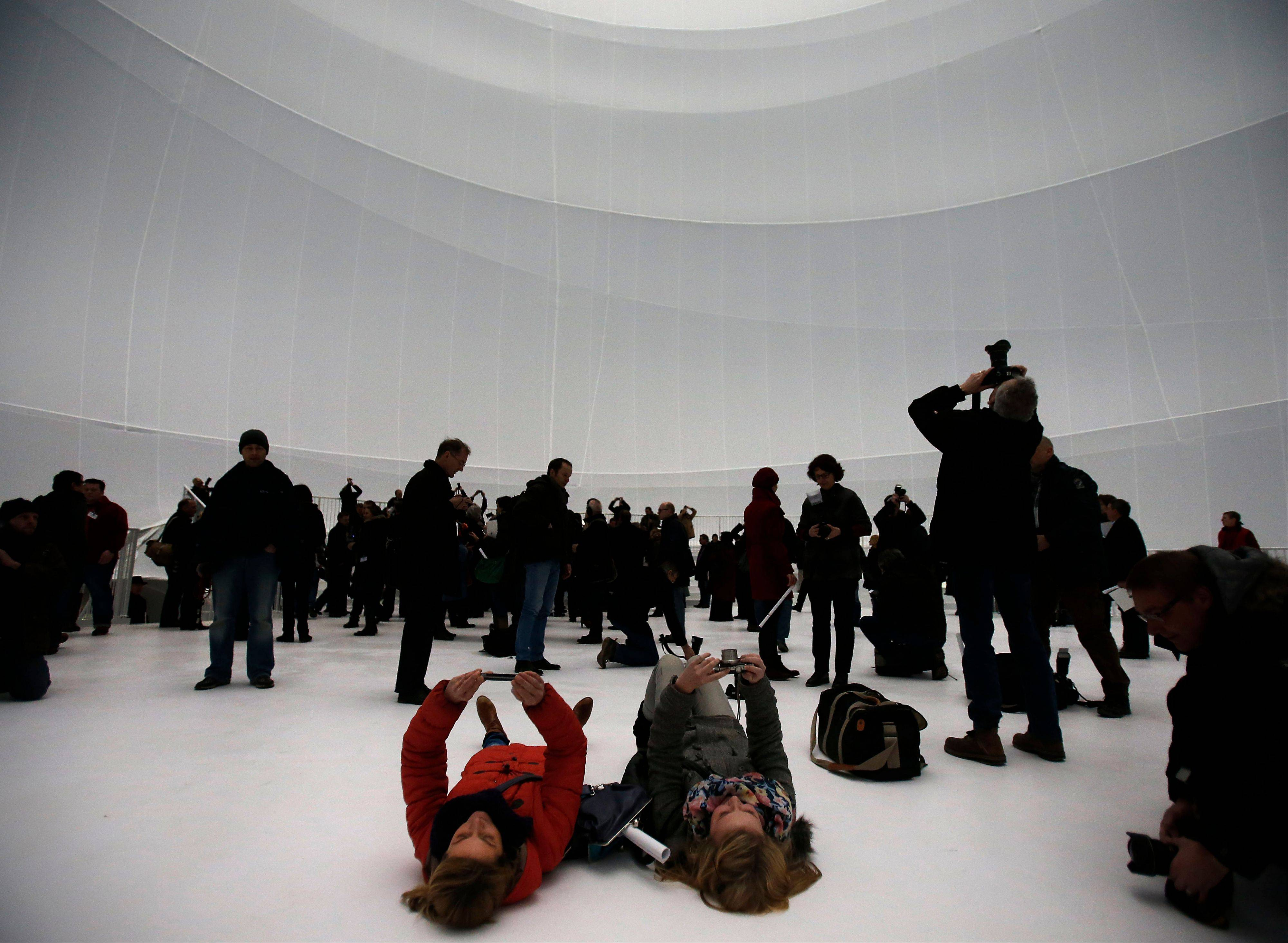 Visitors take pictures Friday inside the installation 'Big Air Package' during the unveiling at the Gasometer in Oberhausen, Germany.