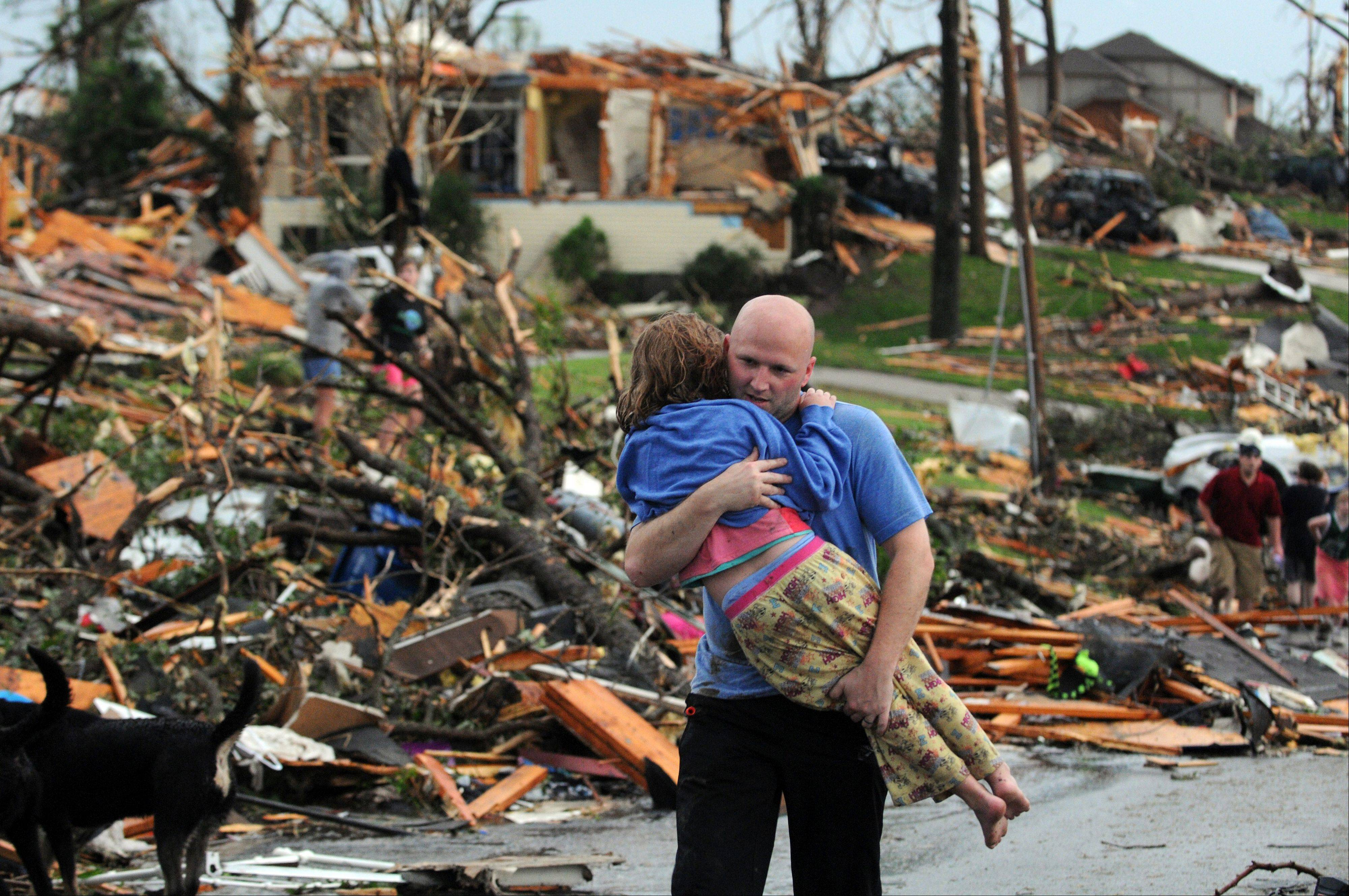 A man carries a young girl who was rescued after a tornado hit Joplin, Mo. In 2011 the United States saw one of the busiest tornado seasons in generations: Nearly 1,700 tornadoes that killed 553 people.
