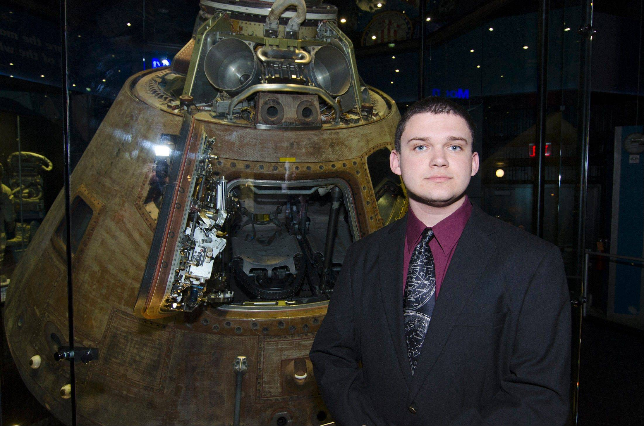 Daniel McGarry of Streamwood stands in front of the Apollo 16 command module at the Honeywell Leadership Challenge.