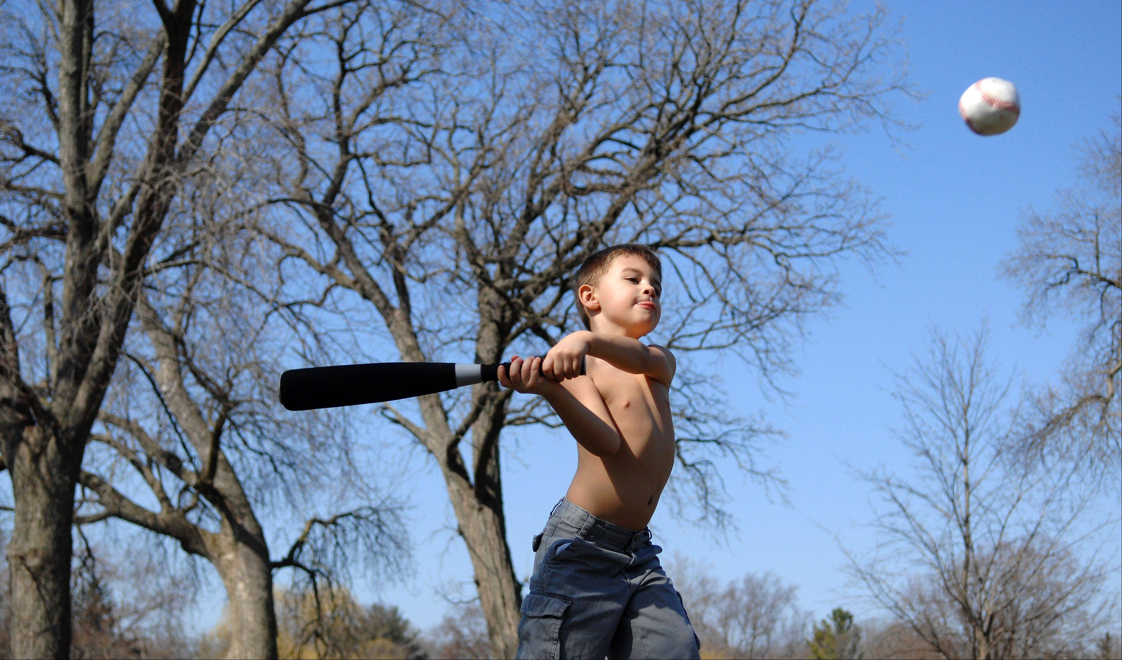 Rick West/Daily Herald, March 2012  Last year in mid-March temperatures hovered around 80 degrees when 5-year-old Adrien Schavone of North Aurora readies his swing while playing baseball with his dad at Island Park in Geneva.