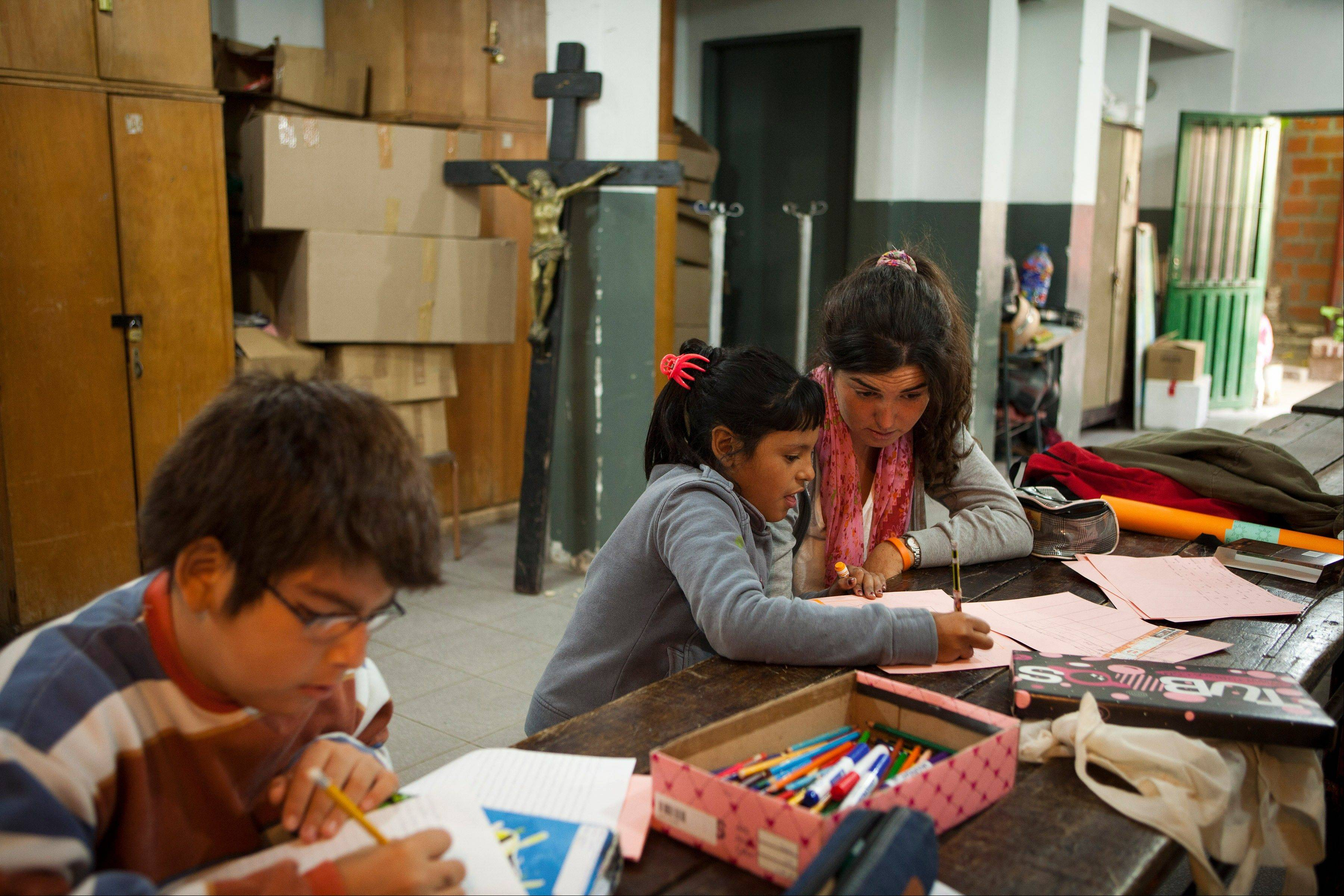 Volunteer Constanza Lascumbres, top right, teaches reading to Nicole Farias, 9, at the Virgin of Caacupe church in a shantytown in Buenos Aires, Argentina. At Villa 21-24, a slum so dangerous that most outsiders wouldn't dare go in, Jorge Mario Bergoglio often showed up unannounced over the course of more than 20 years. For many at the slum's Caacupe Virgin of the Miracles Church, it's nothing short of a miracle that the same man is now the pope.