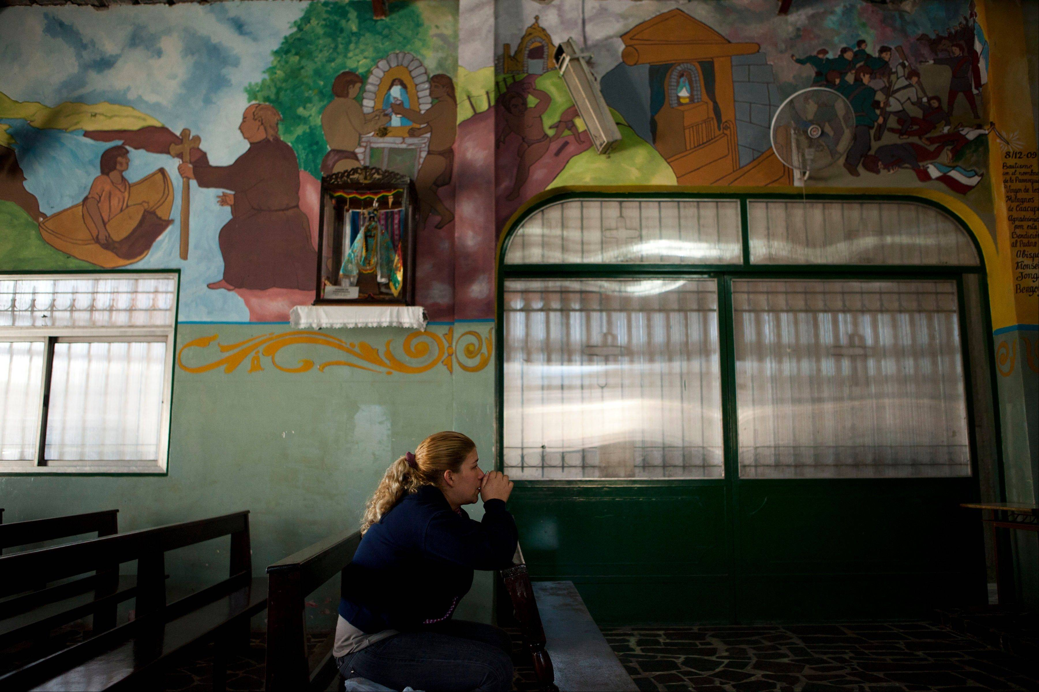 A woman prays inside the Virgin of Caacupe Church in the Villa 21-24 shantytown in Buenos Aires, Argentina. Residents here proudly recall how the Buenos Aires Archbishop Jorge Mario Bergoglio would walk in arrive on a bus and walk through the mud to reach the young members of the slum's church. How he sponsored marathons and carpentry classes, consoled single mothers, blessed the local chapel and washed the feet of recovering drug addicts. How he became one of them.