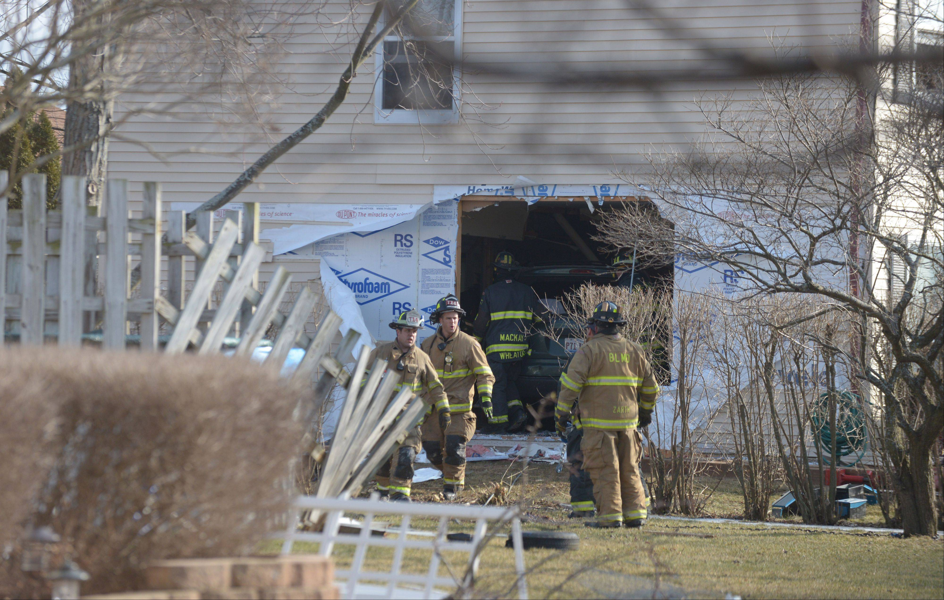 Carol Stream police and firefighters clear a home of wreckage Thursday afternoon after a minivan crashed through the wall of the house on the 600 block of Bluff Street.