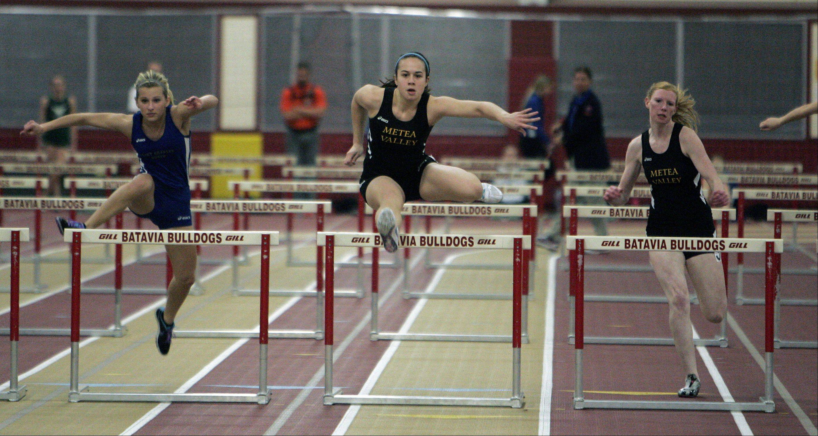 Elizabeth Brandenburg of Metea Valley, center, Jessica Collins, right, also of Metea Valley and Brittney Kostrzewski of St. Charles North head to the finish in the 55 meter hurdles during the Upstate Eight Conference indoor track meet at Batavia High School Friday.