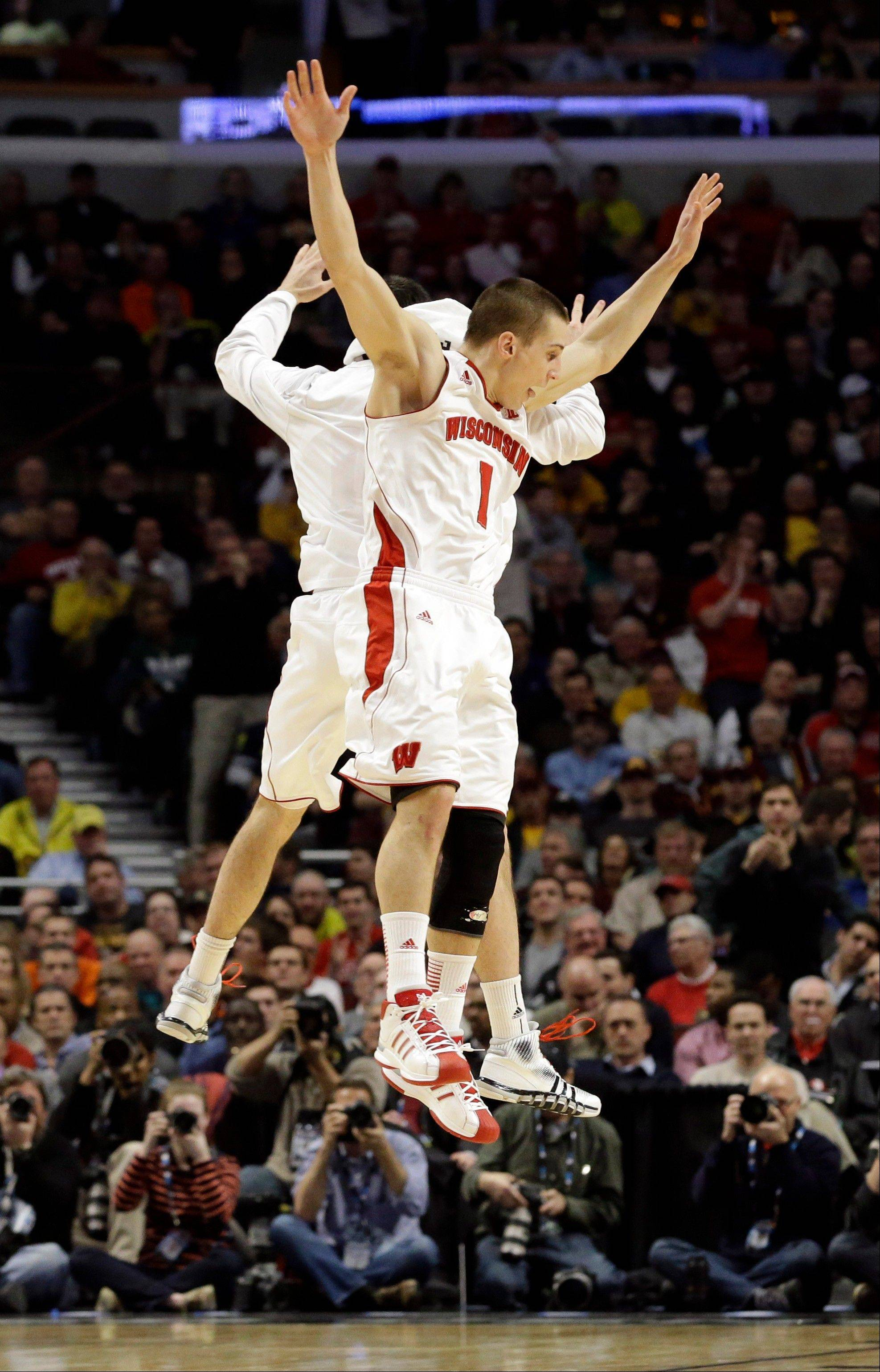 Wisconsin's Ben Brust (1) celebrates with a teammate during the second half of an NCAA college basketball game at the Big Ten tournament against MichiganFriday, March 15, 2013, in Chicago. Wisconsin won 68-59.