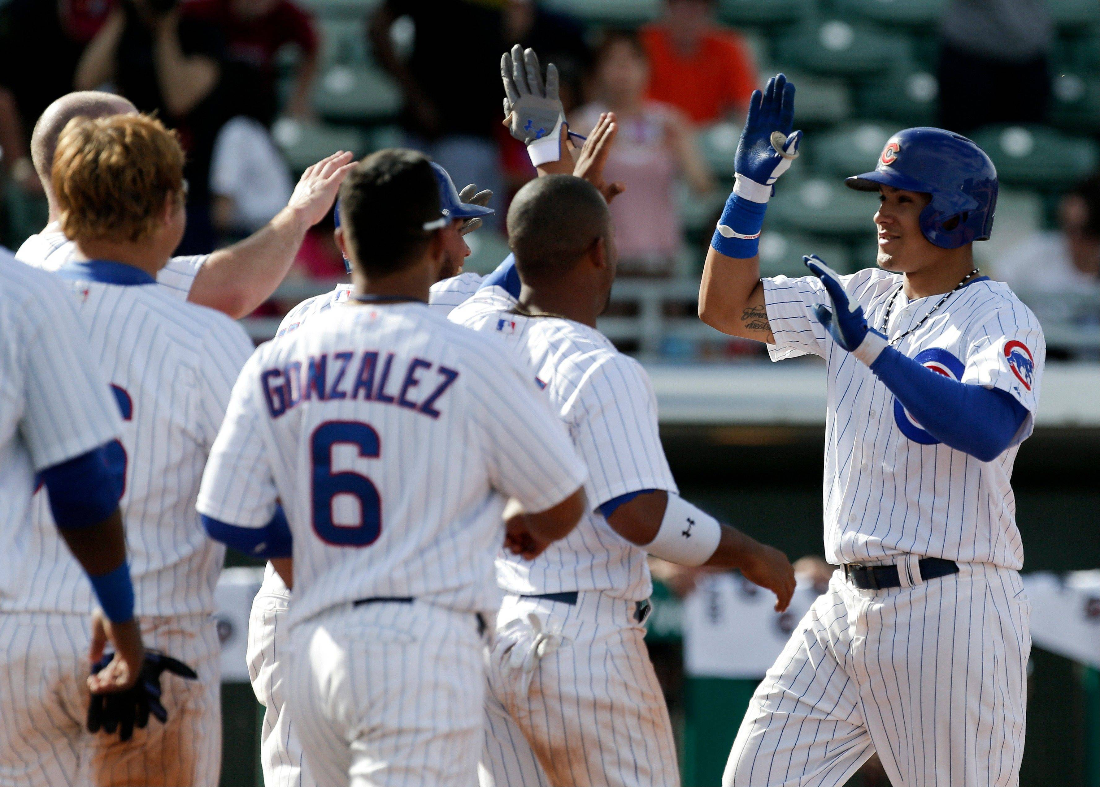 Javier Baez, right, celebrates his walk off 2-run home run against Japan during the bottom the ninth inning of an exhibition spring training baseball game in Mesa, Ariz. Friday, March 15, 2013.