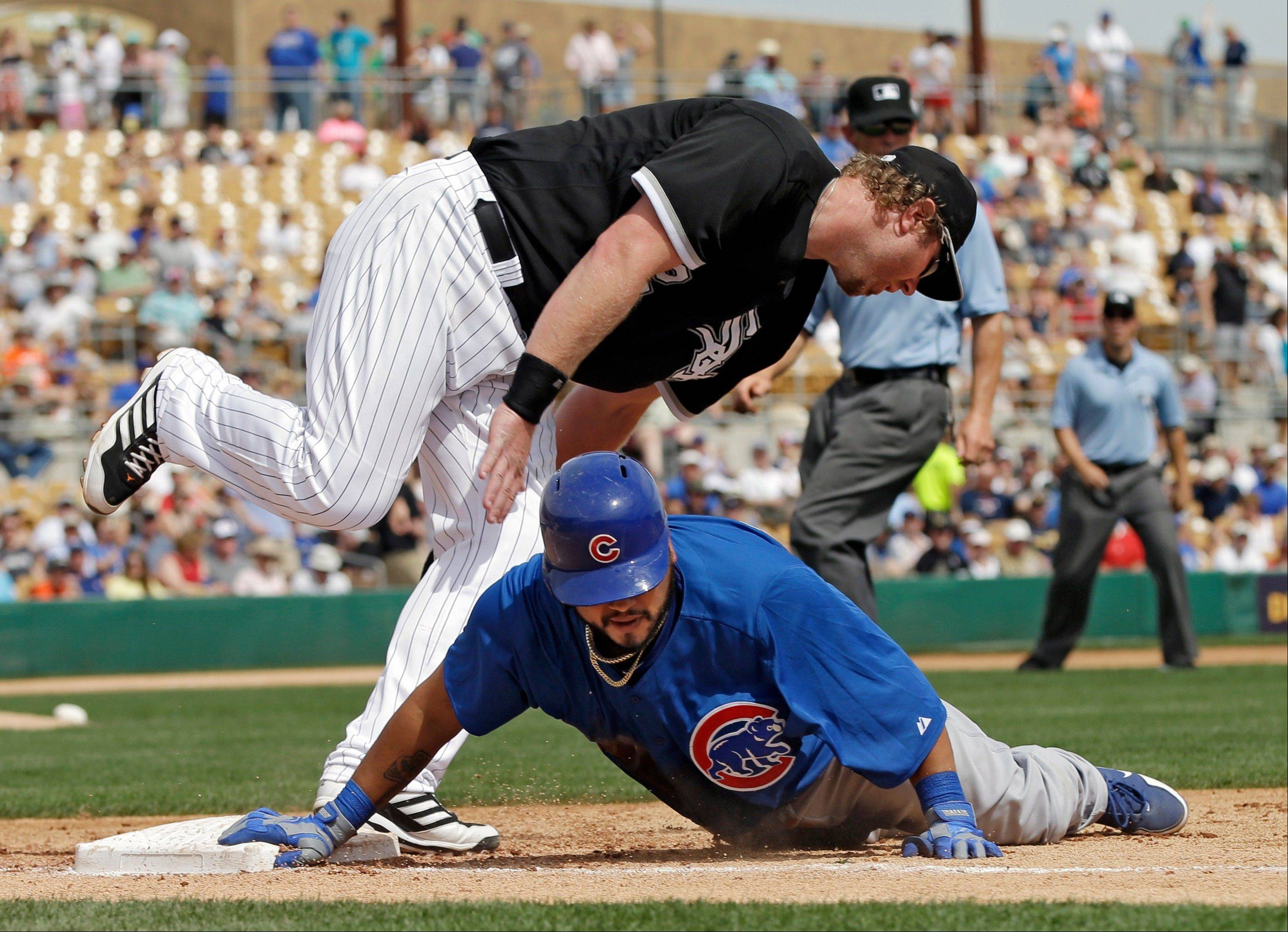 Dioner Navarro dives back to first under Chicago White Sox first baseman Adam Dunn after an RBI single in the fourth inning of an exhibition spring training baseball game Friday, March 15, 2013, in Glendale, Ariz.