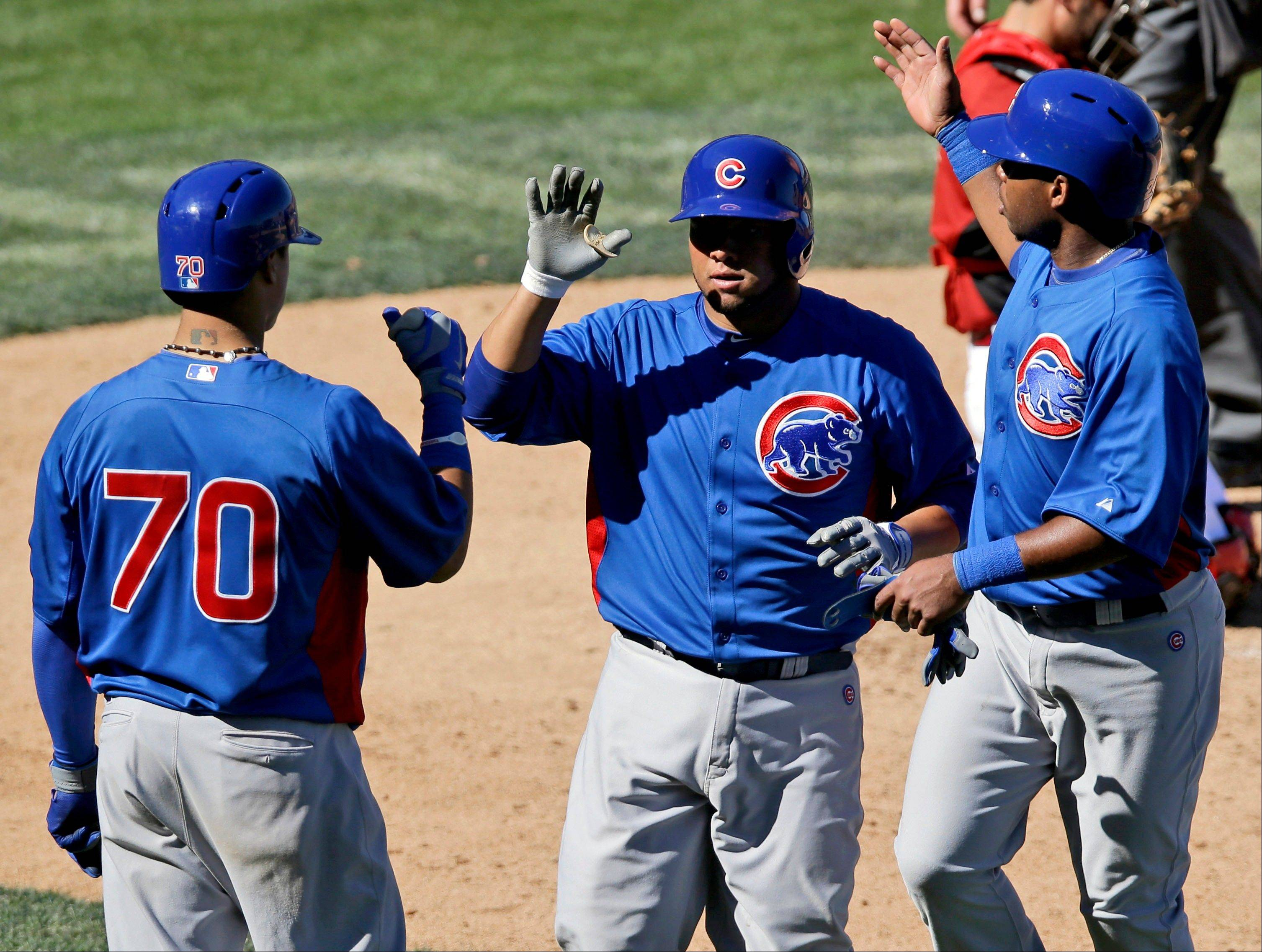 Chicago Cubs' Welington Castillo, center, is greeted at home plate by Javier Baez (70) and Luis Valbuena, right, after his two-run home run against the Arizona Diamondbacks during the sixth inning of an exhibition spring training baseball game, Monday, March 11, 2013, in Scottsdale, Ariz.