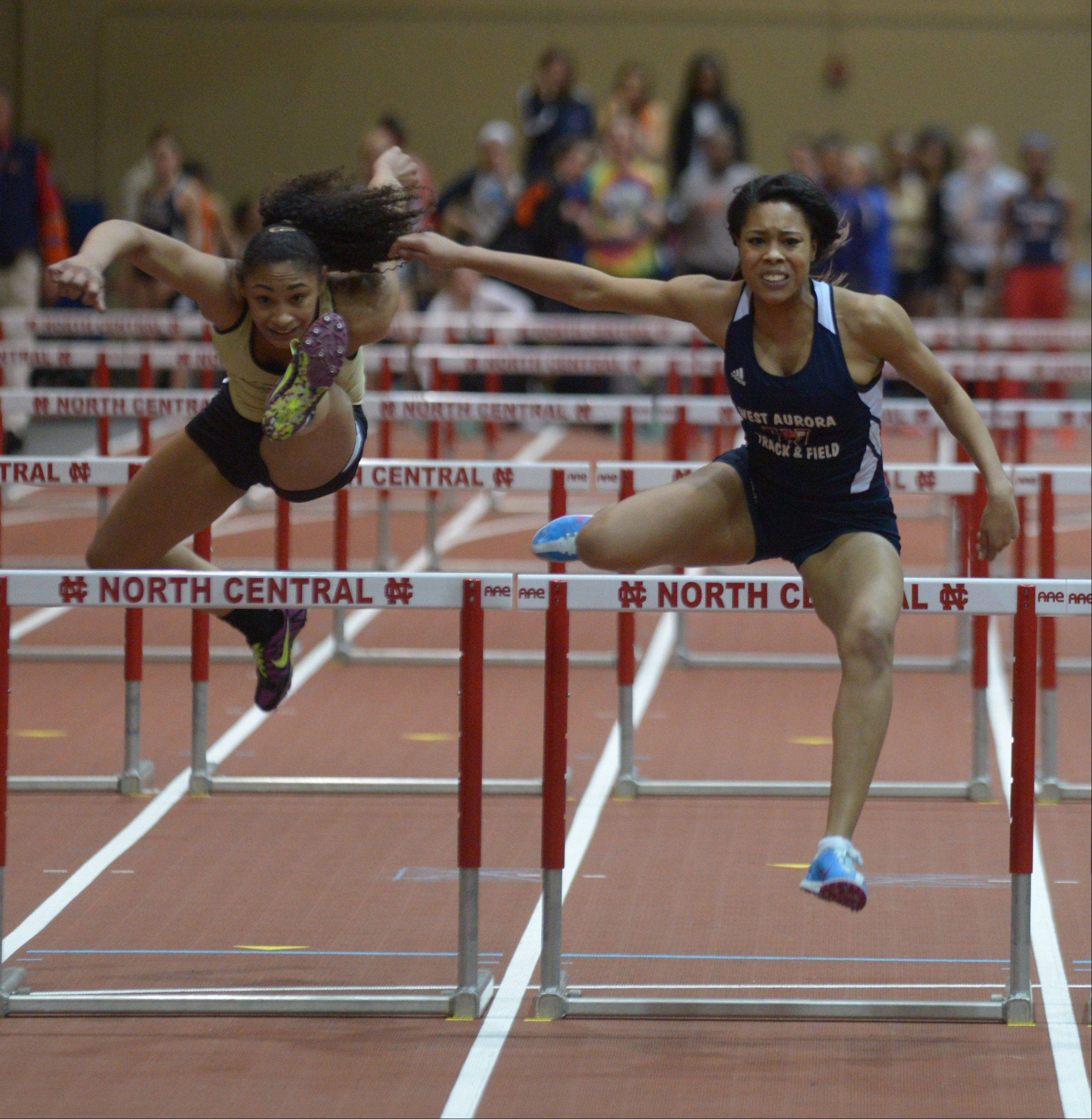 Kailey James,left, of Glenbard North and Tykia Neal of West Aurora take part in the 55 meter hurdles during the DuPage Valley Conference girls indoor track meet at North Central College Thursday.