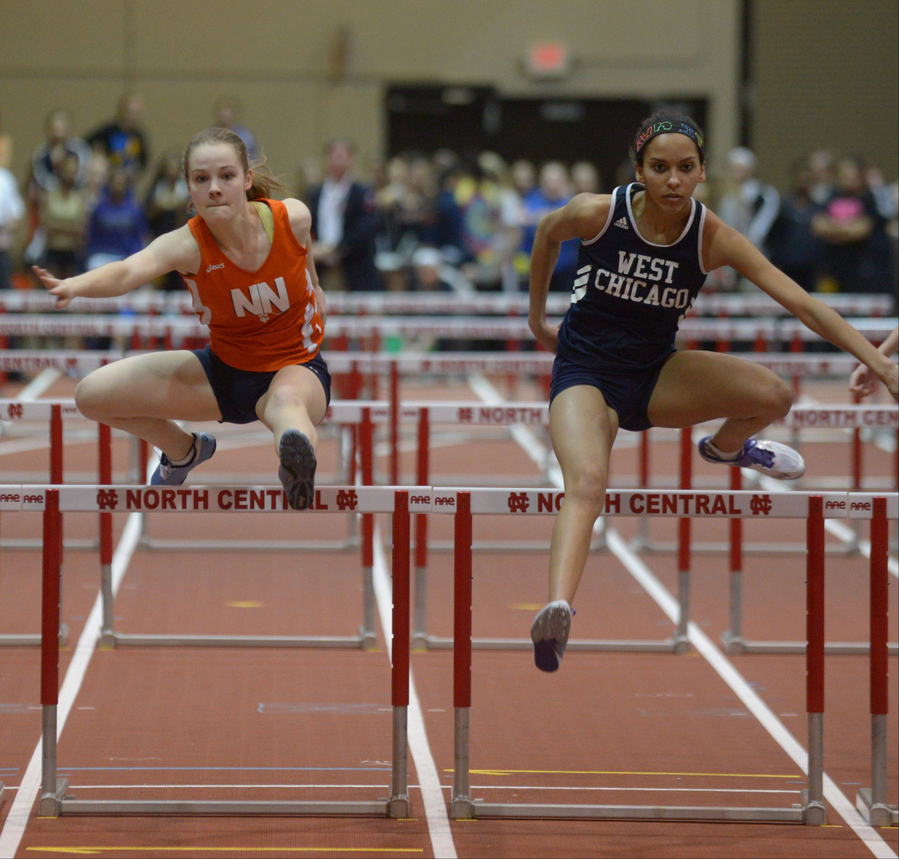 Sarah Triner of West Chicago,left, and Emily Painter of Naperville North are neck and neck in the 55 meter hurdles at the DuPage Valley Conference girls indoor track meet.