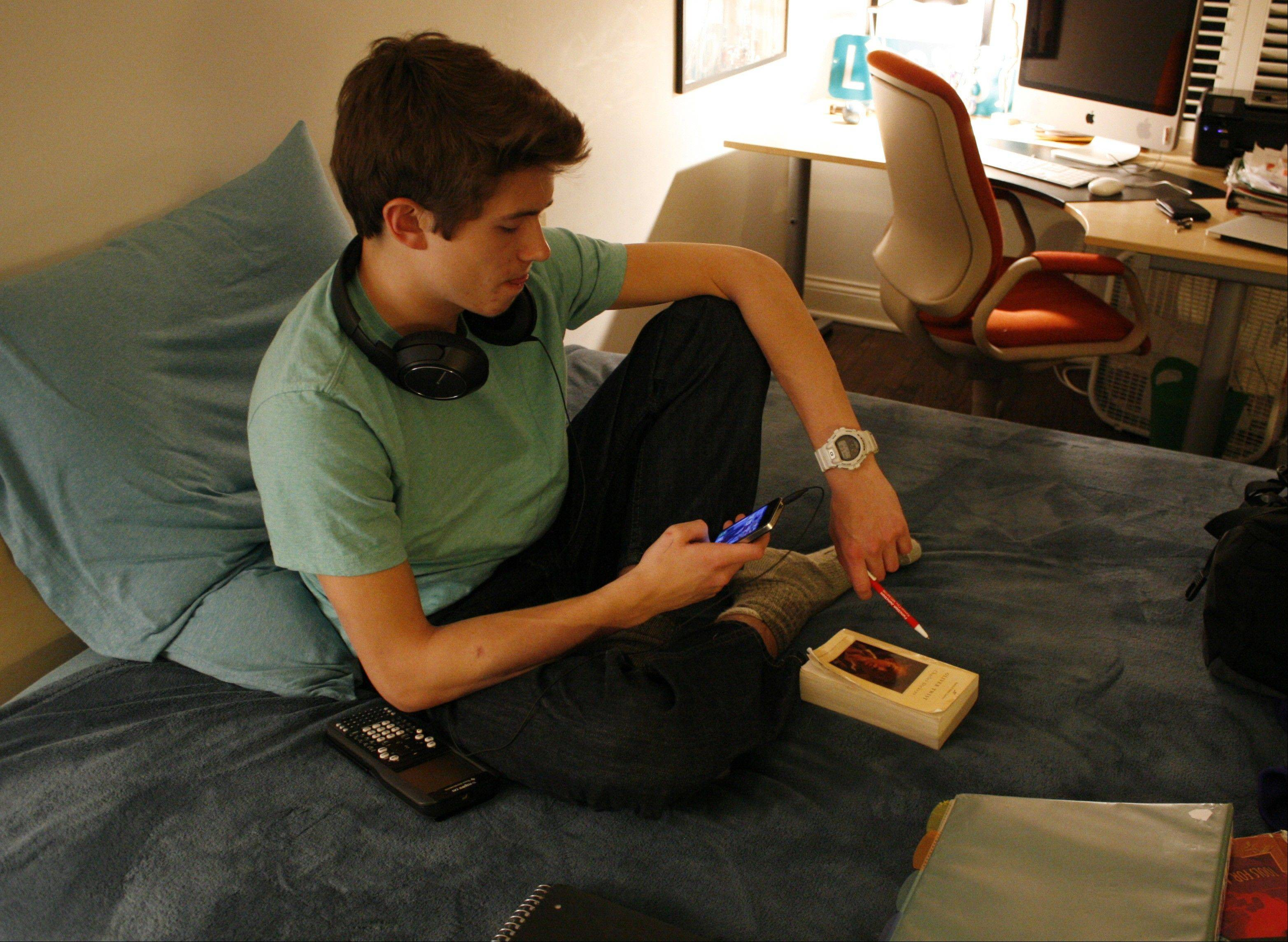 Donald Conkey, 15, checks his smartphone Monday while doing homework in his bedroom in Wilmette. A new report from the Pew Internet & American Life Project says more teens are using smartphones as a main means of accessing the Internet — more so than adults.