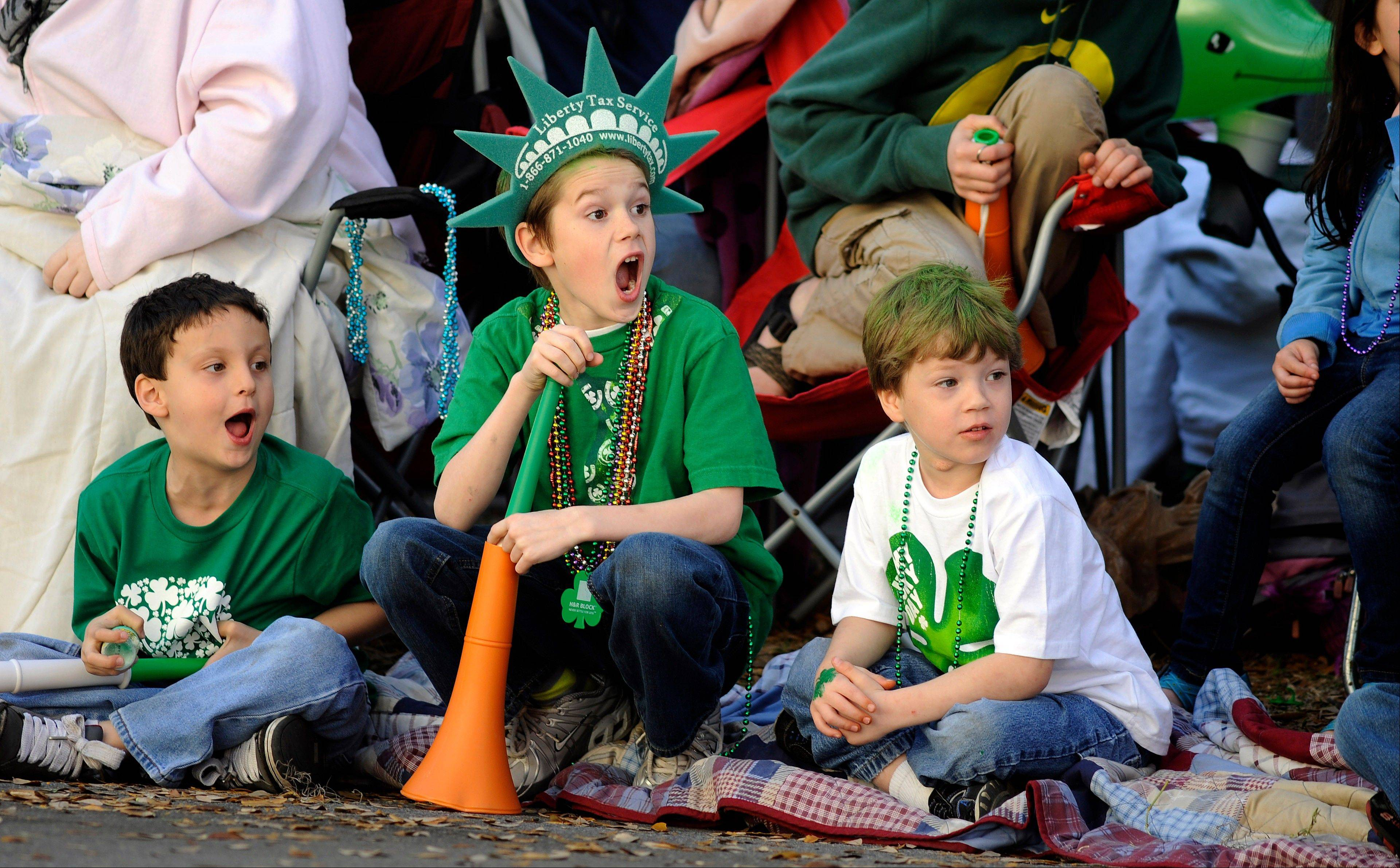 Jacob Tidwell, center, and his friends Donavan Mock, left, and Preston Vasquez react Saturday to a band during Savannahís 189-year-old St. Patrick's Day parade.