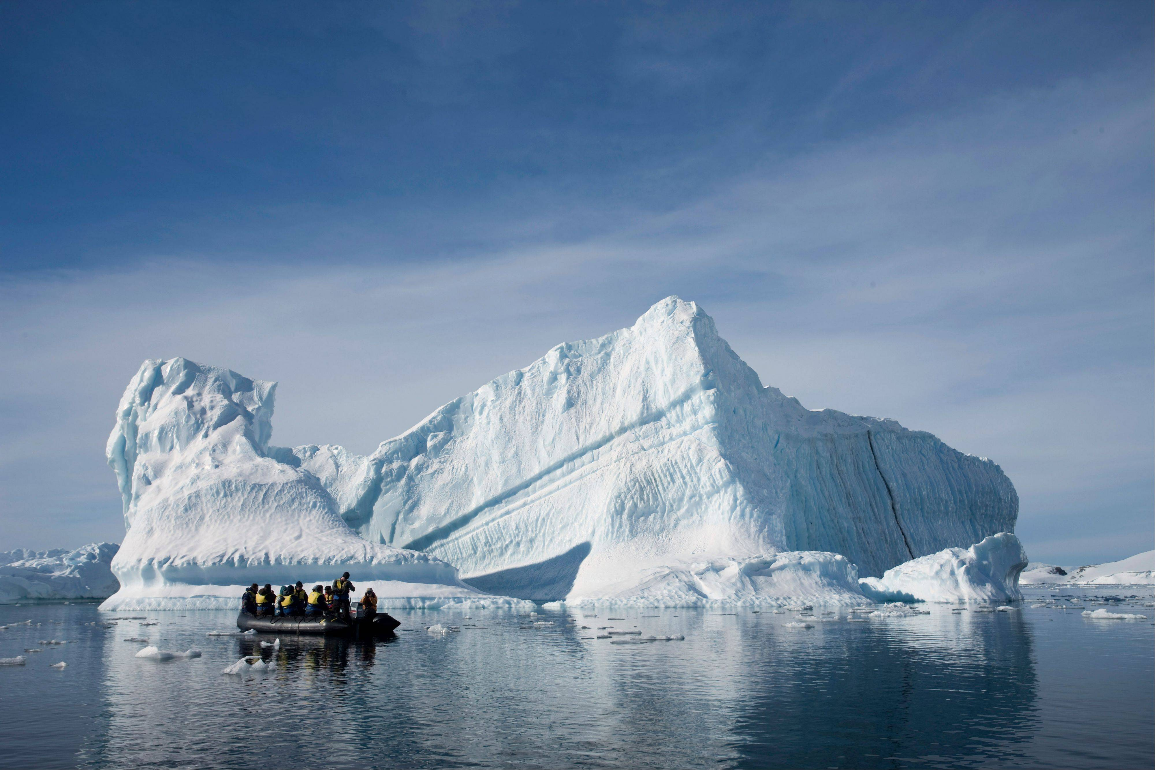 Associated Press/Dec. 1, 2009 An inflatable boat carries tourists past an iceberg along the Antarctic Peninsula.