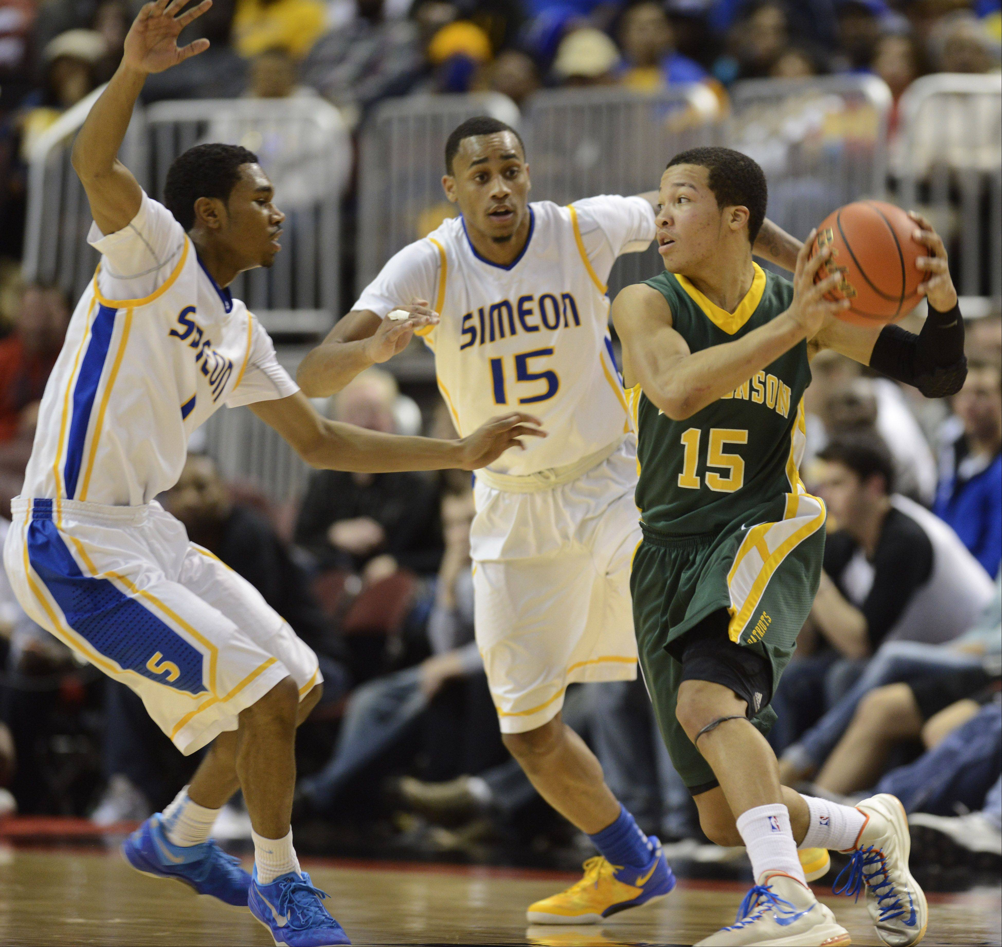 Stevenson's Jalen Brunson, right, gets double-teamed by Simeon's Jaylon Tate, left, and Russell Woods during the Class 4A boys basketball state finals at the Carver Arena in Peoria Saturday.