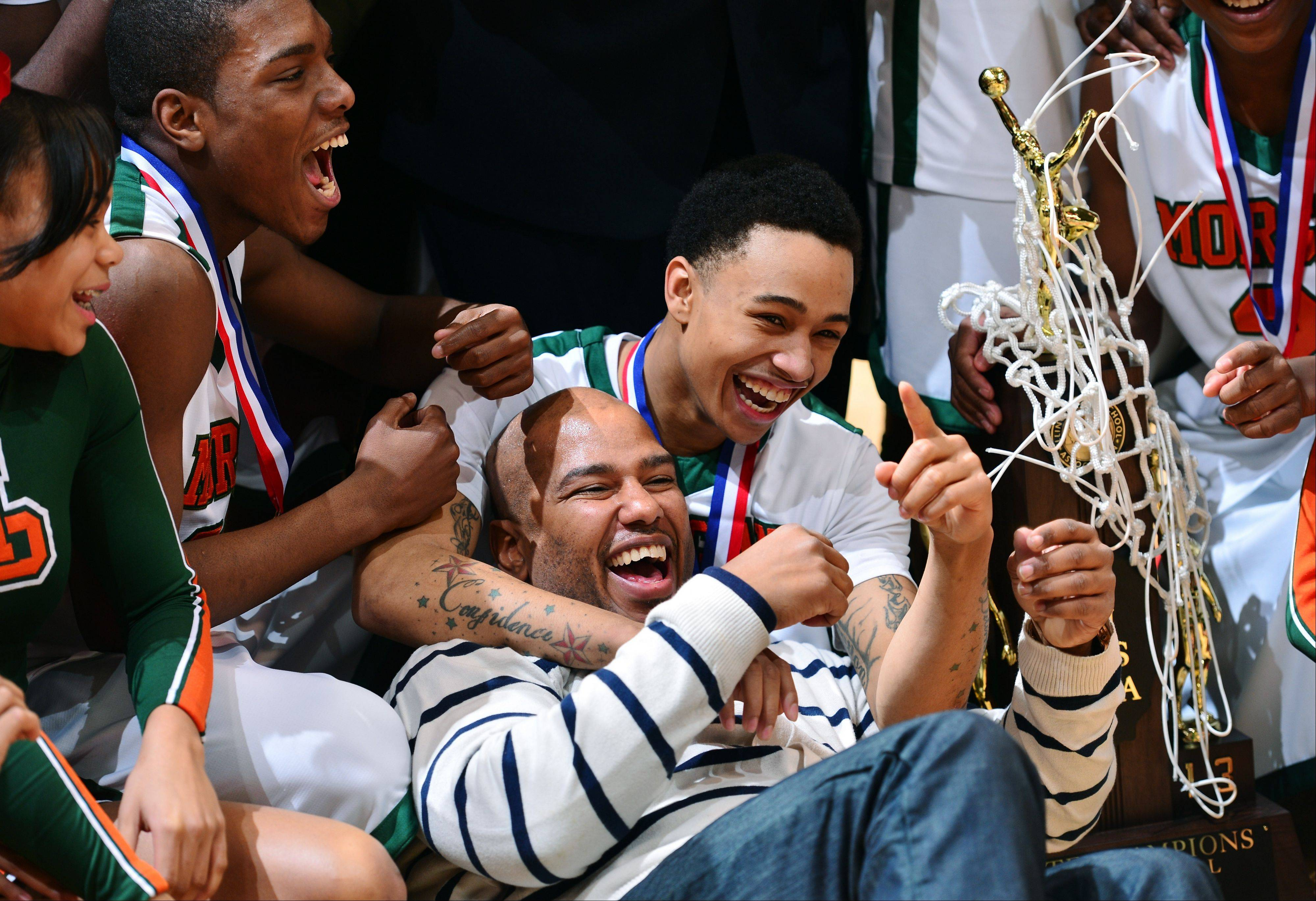 Morgan Park's Kyle Davis, middle, celebrates with former coach Che Chapel and teammates after the Mustangs' 63-48 win over Cahokia in Saturday's Class 3A state championship game in Peoria.