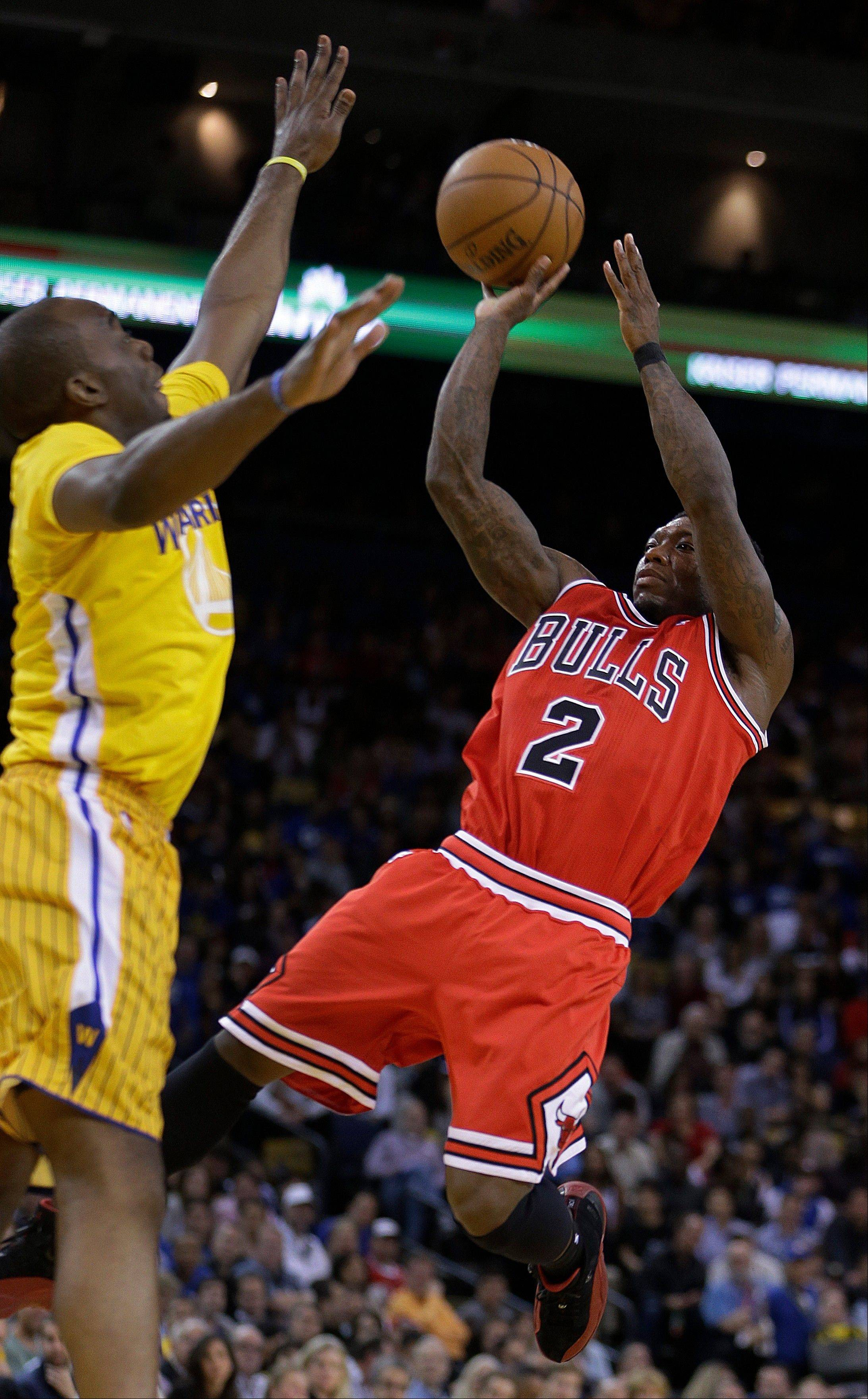 Chicago Bulls' Nate Robinson, right, shoots against Golden State Warriors' Carl Landry during the first half of an NBA basketball game Friday, March 15, 2013, in Oakland, Calif. (AP Photo/Ben Margot)