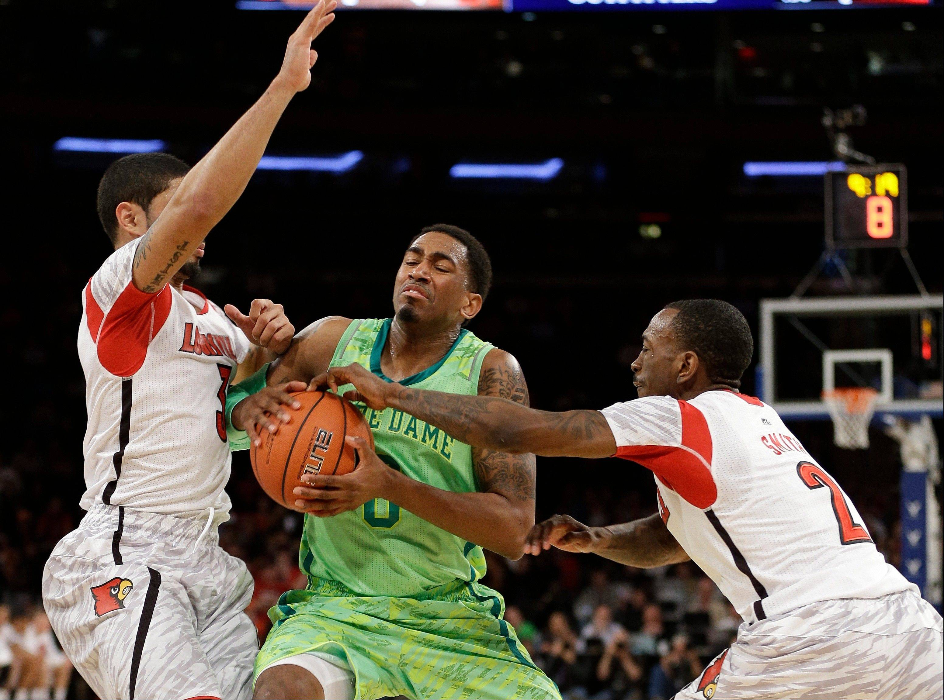 Notre Dame's Eric Atkins (0) moves between Louisville's Russ Smith (2) and Peyton Siva (3) during the second half of an NCAA college basketball game at the Big East Conference tournament Friday, March 15, 2013, in New York. Louisville won 69-57. (AP Photo/Frank Franklin II)