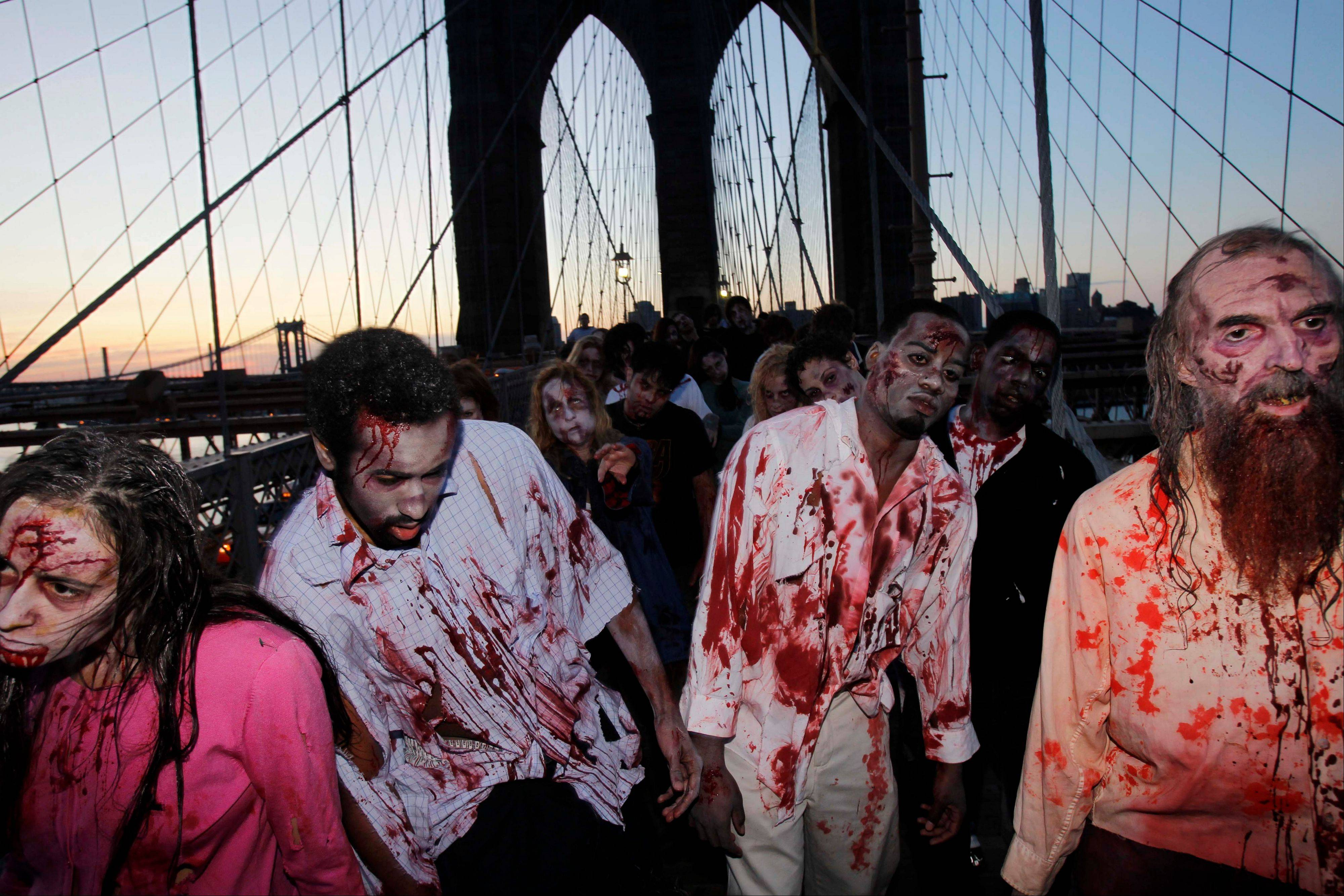 "Costumed actors shamble along the Brooklyn Bridge in New York, promoting the Halloween premiere of the AMC television series ""The Walking Dead."" Clemson University English professor Sarah Lauro says people are more interested in zombies when they're dissatisfied with society as a whole."