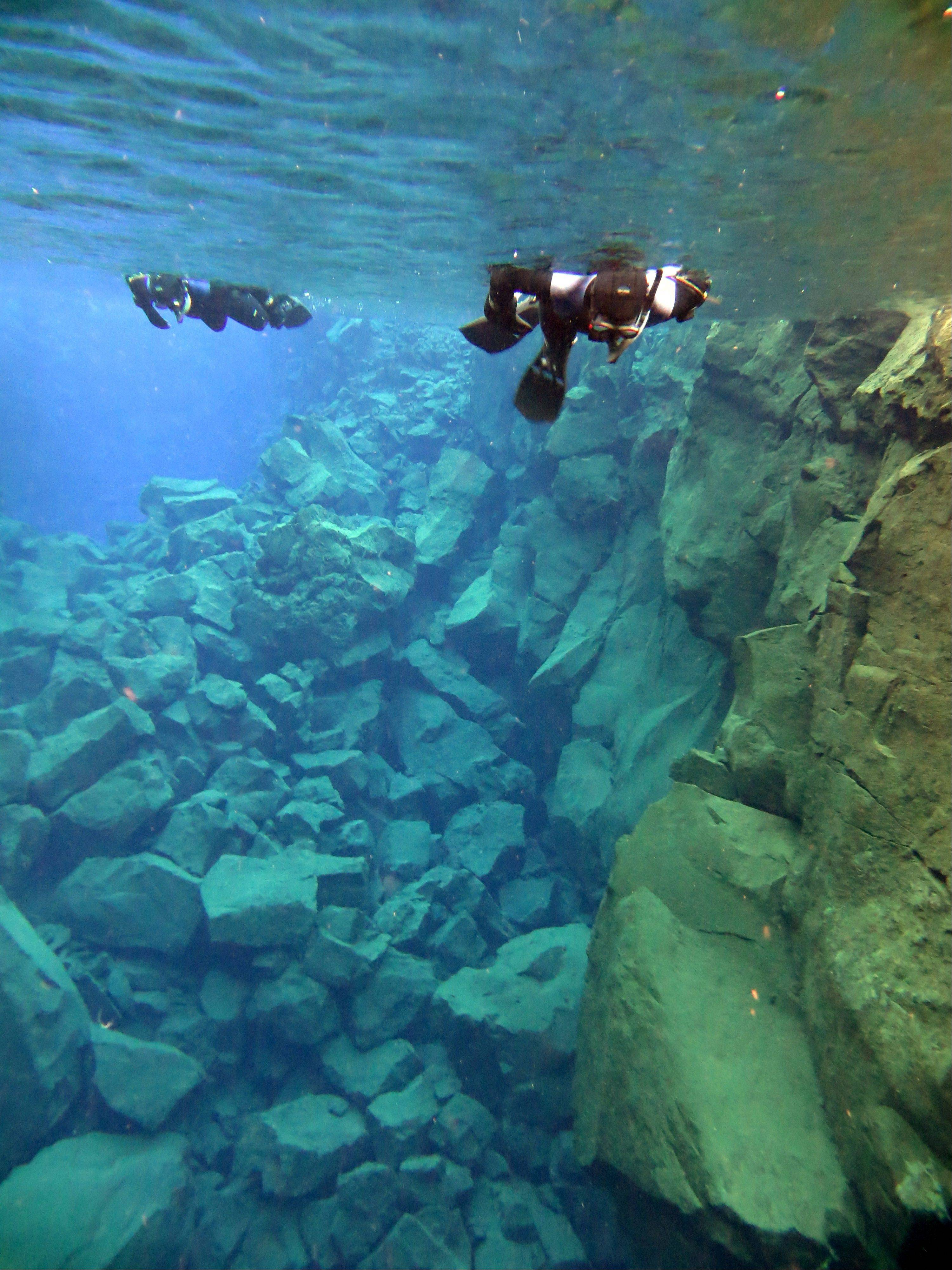 Snorkelers traverse the popular Silfra rift in Iceland. Despite its near-freezing temperatures, Silfra has become a popular site for divers.