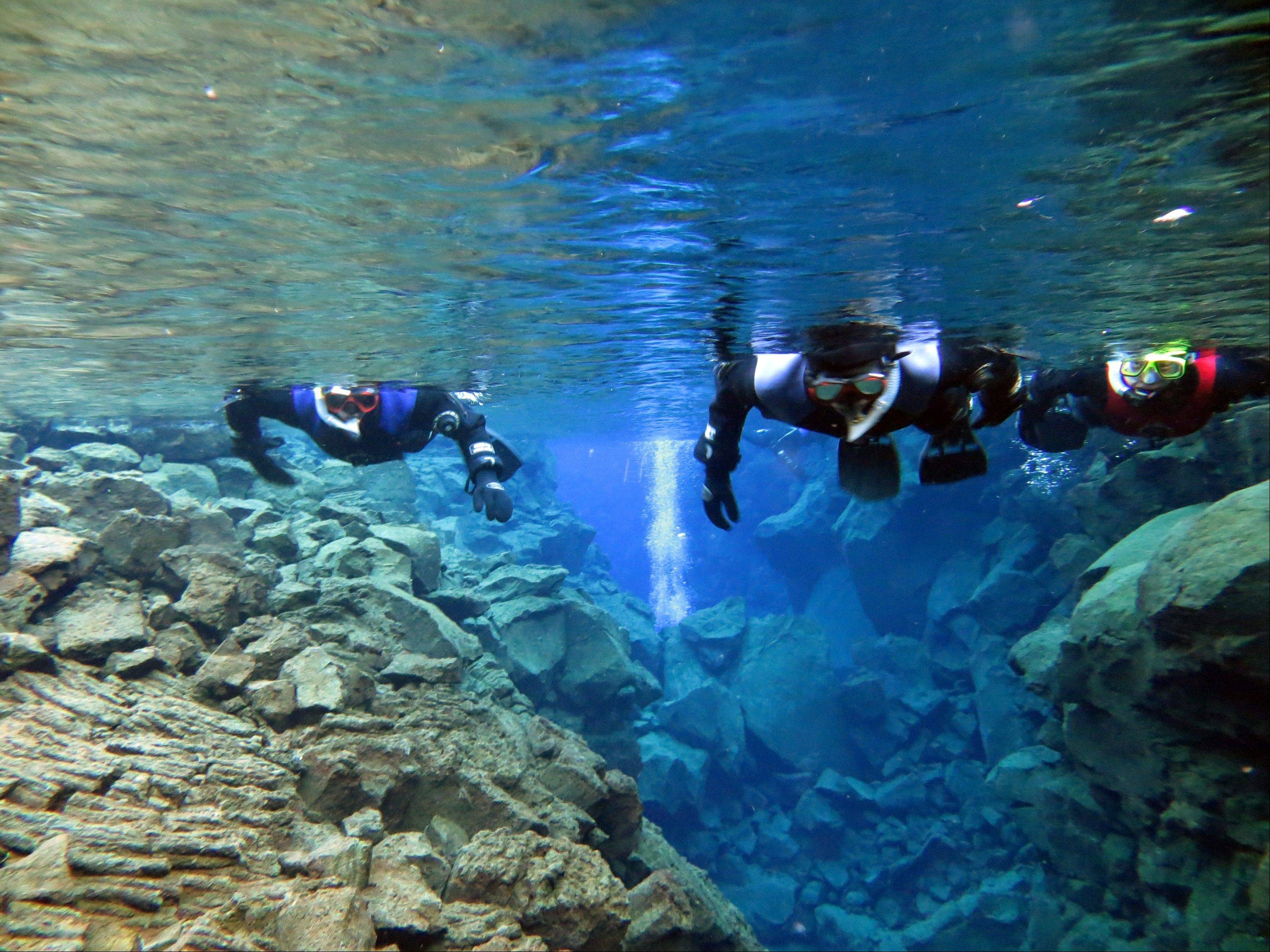 Snorkelers traverse Iceland's Silfra, a rift fed by glacier water. Because of its pure water and stunning colors, Silfra has become a popular site for divers despite near-freezing temperatures.