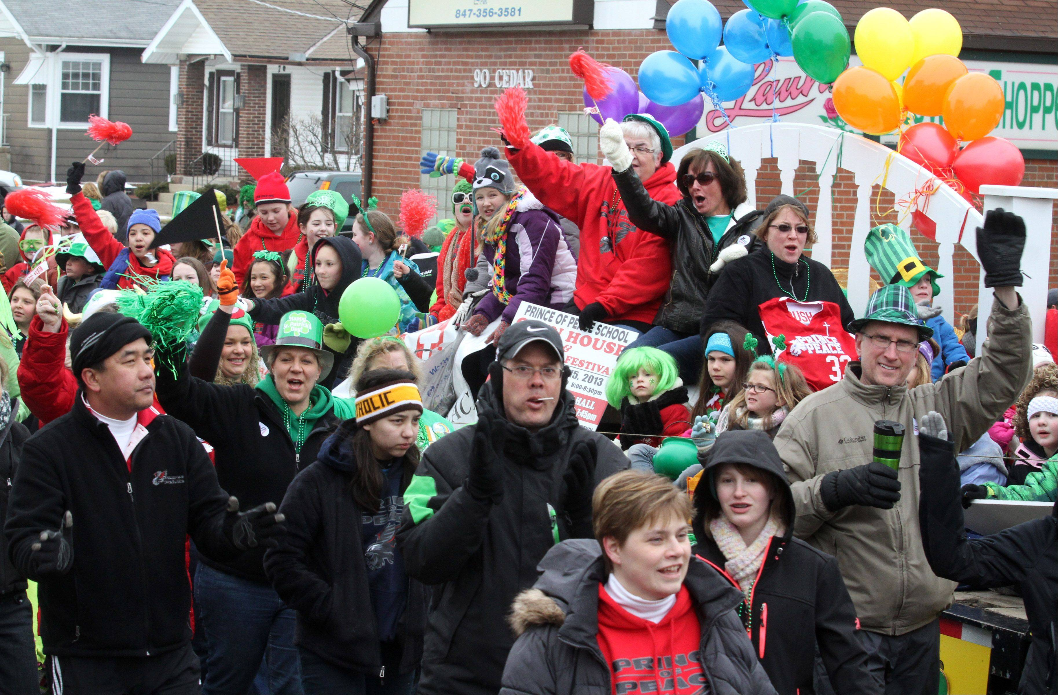 Parade participants riding on the Fox Recovery and Towing flatbed float toss candy to children Saturday during the Lake Villa St. Patrick's Day parade.