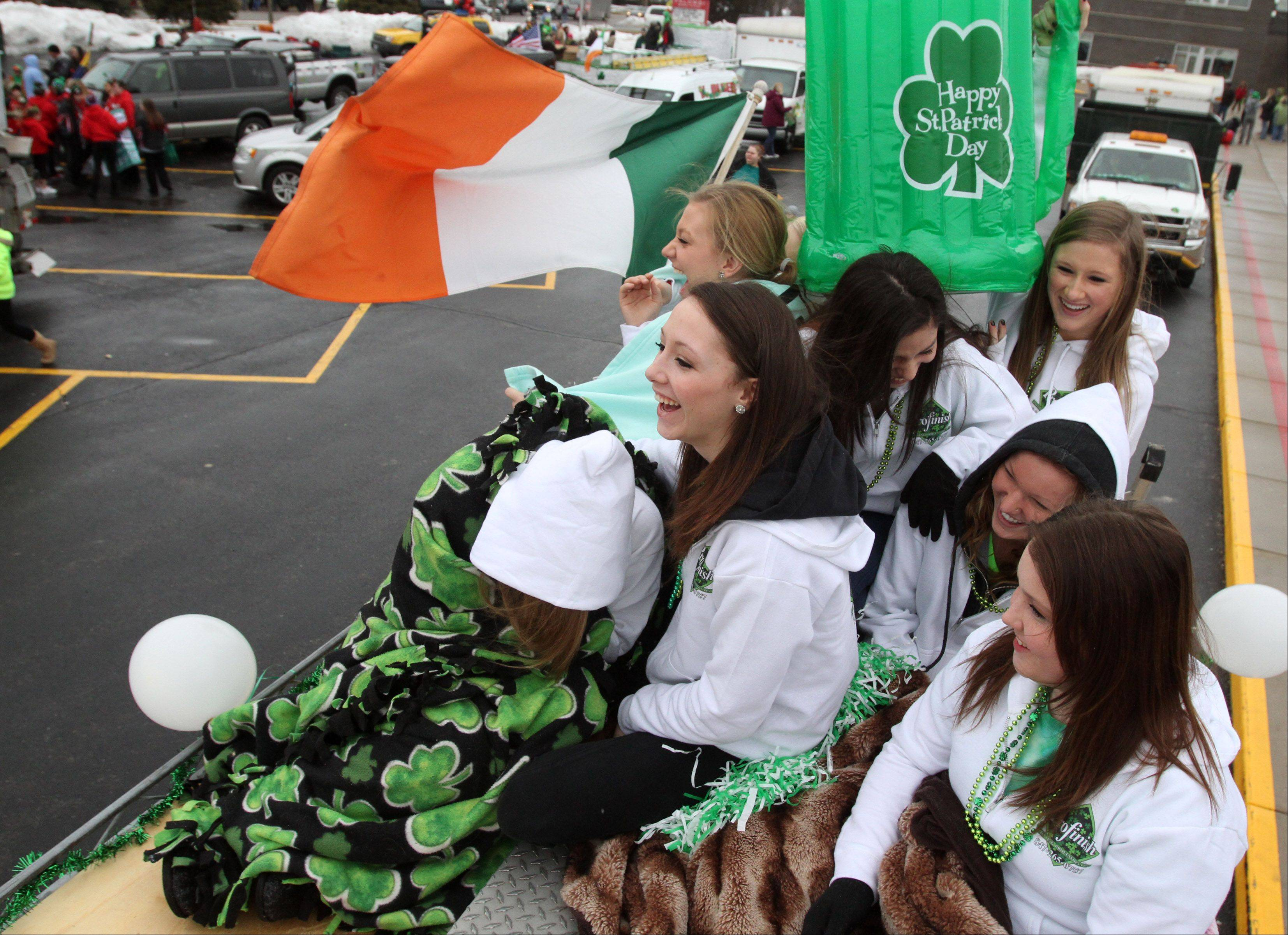Lake Zurich High School students including Sara Cook, 14, and front row left to right, Ashlee Cook, 15, and Mackenzie Matthews, 14, all of Lake Villa, prepare to ride on the Profinish Painting Professionals of Lake Villa van Saturday in the Lake Villa St. Patrick's Day parade.