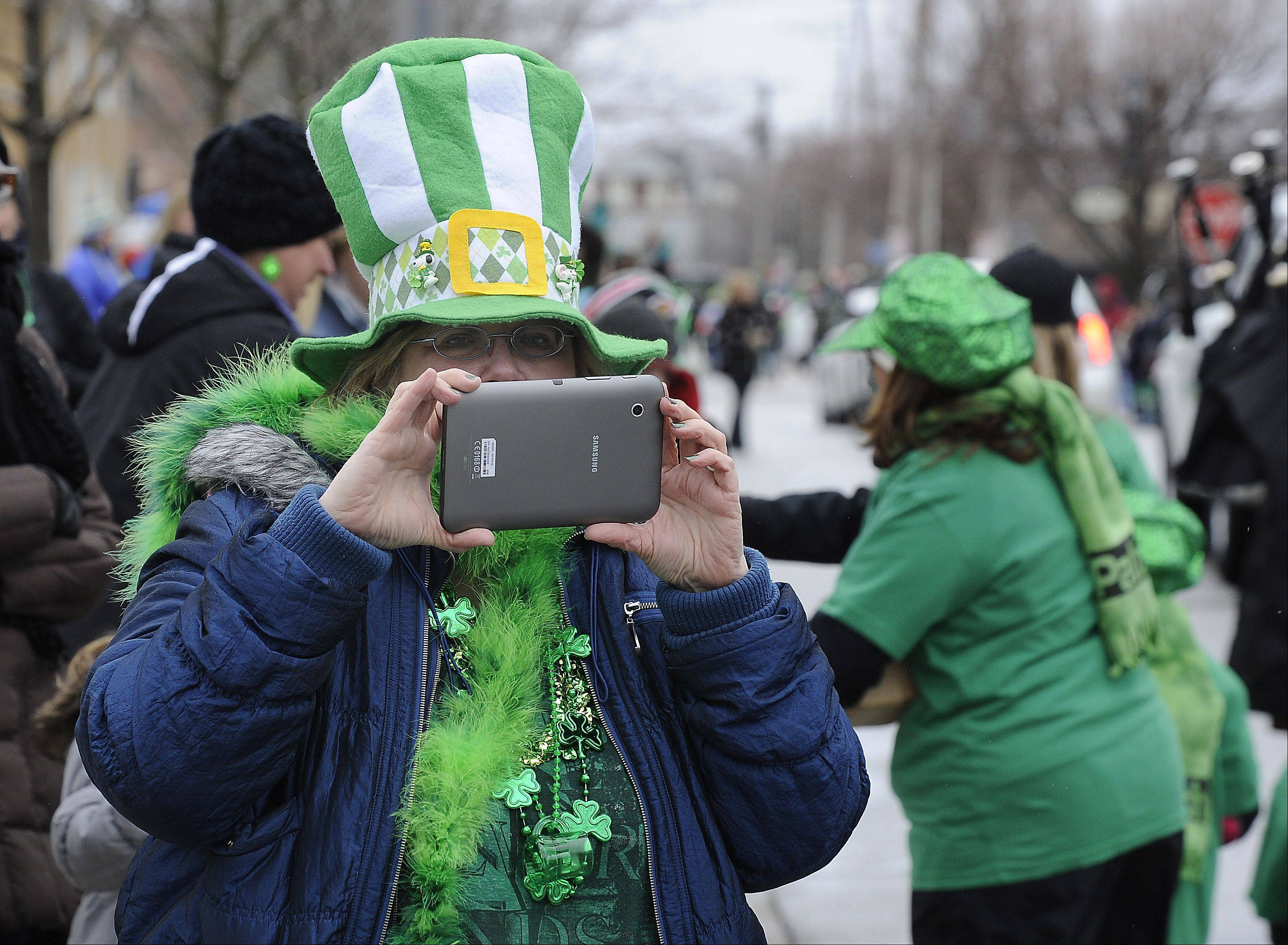 Despite the cold and the snow showers Saturday, Vivian Garcia of Poplar Grove captures the moment at the St. Patrick's Day parade in Palatine.