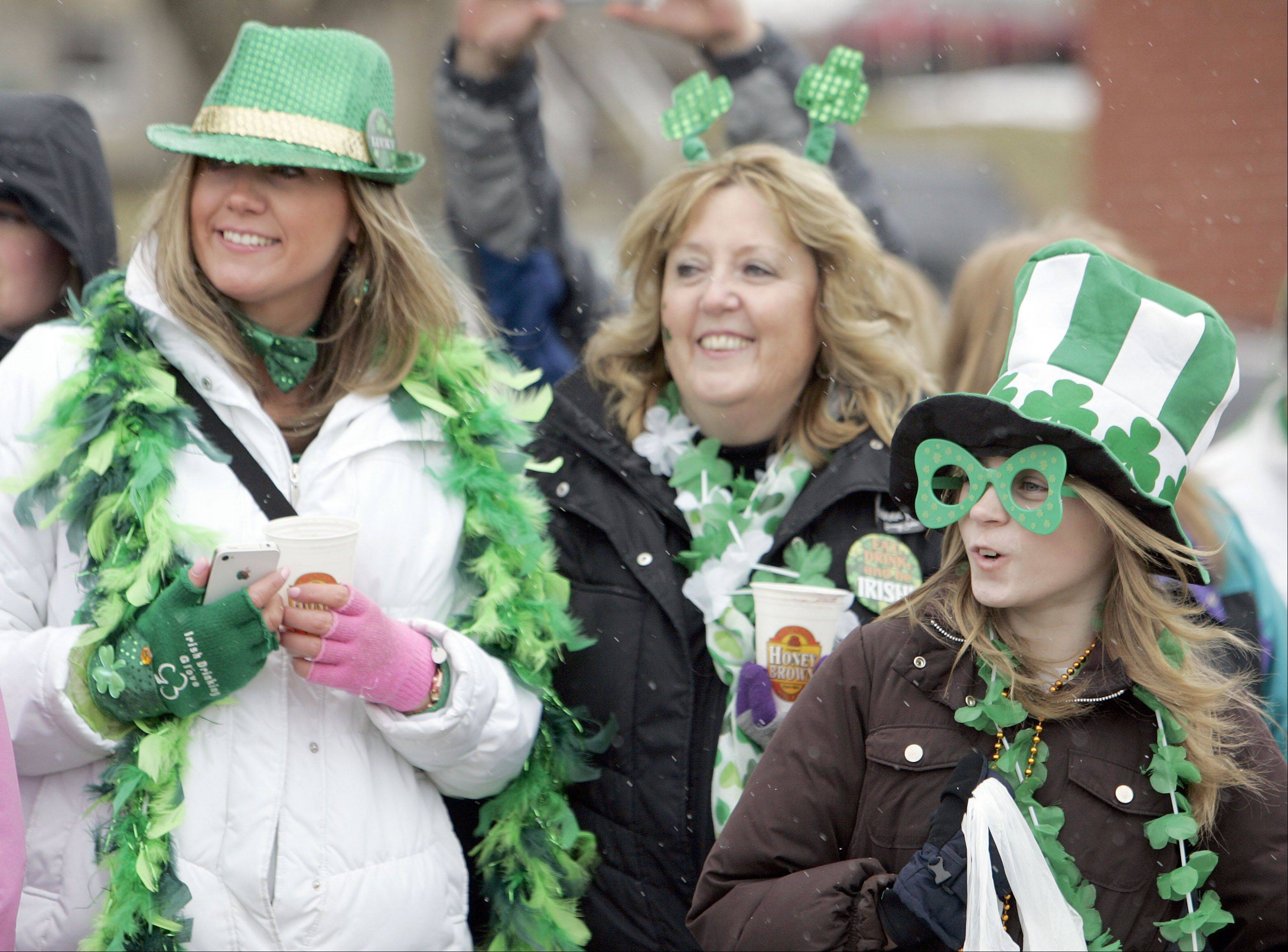 Three generations -- including Carrie Greenhagel, left, Peggy Greenhagel and Morgan Payne, 11, all of Huntley, braved the 30 degree weather Saturday to watch the Thom McNamee Memorial St. Patrick's Day Parade in East Dundee.